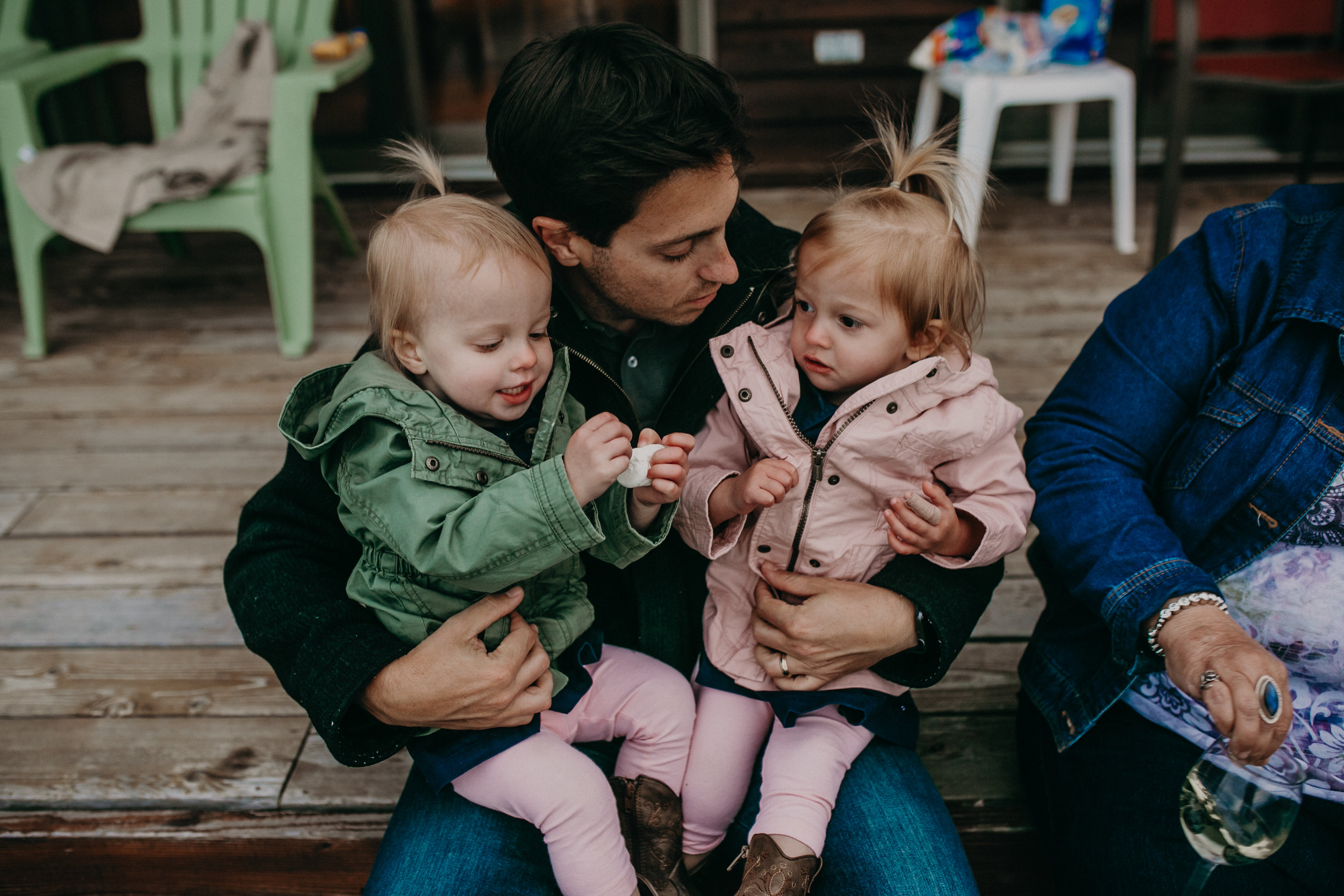 Andrea Wagner Photographer captures sweet moments between twin toddlers and their dad during a lifestyle family photo shoot on Madeline Island