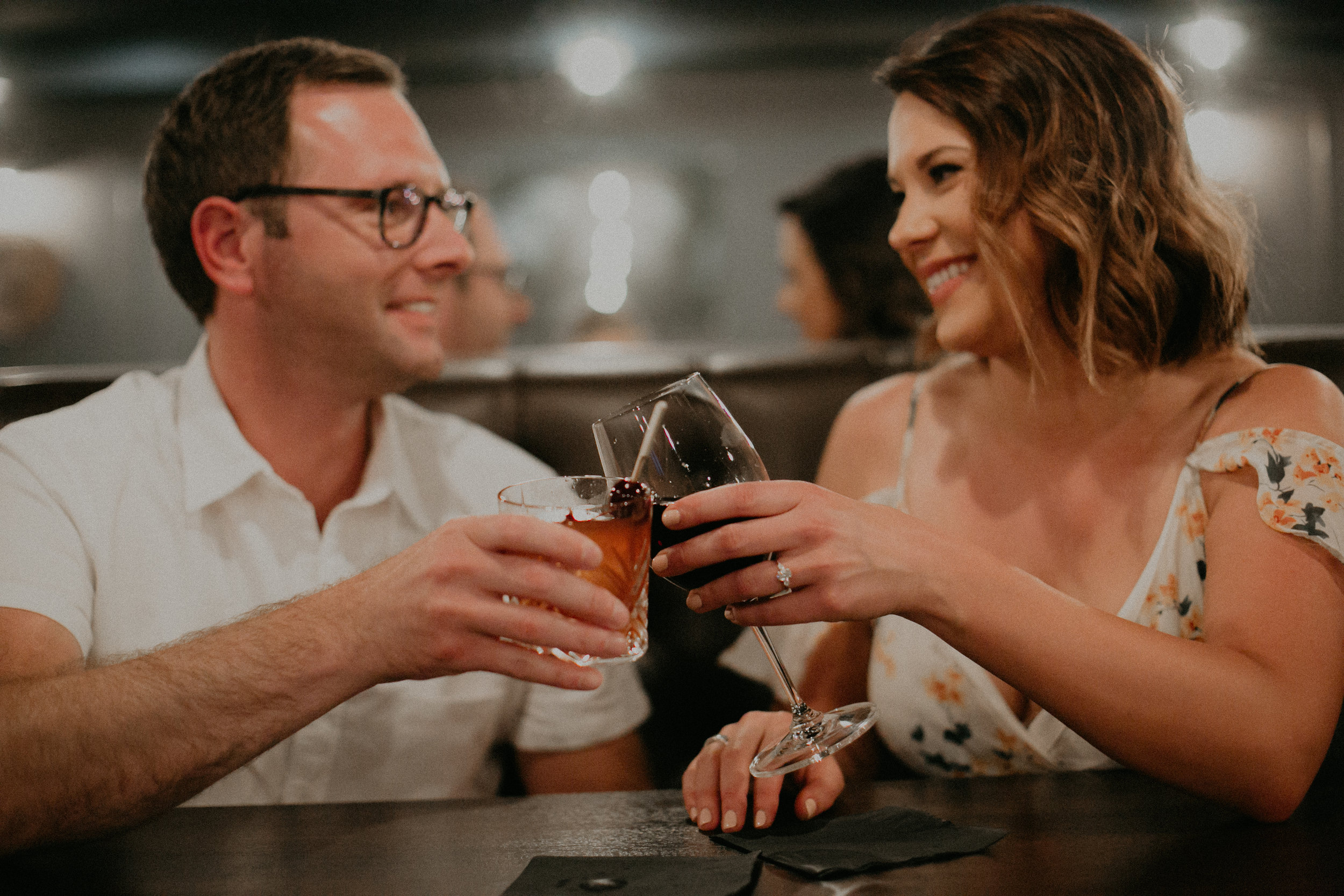 a couple cheers their drinks at LoLo American Kitchen in Hudson WI during their engagement session