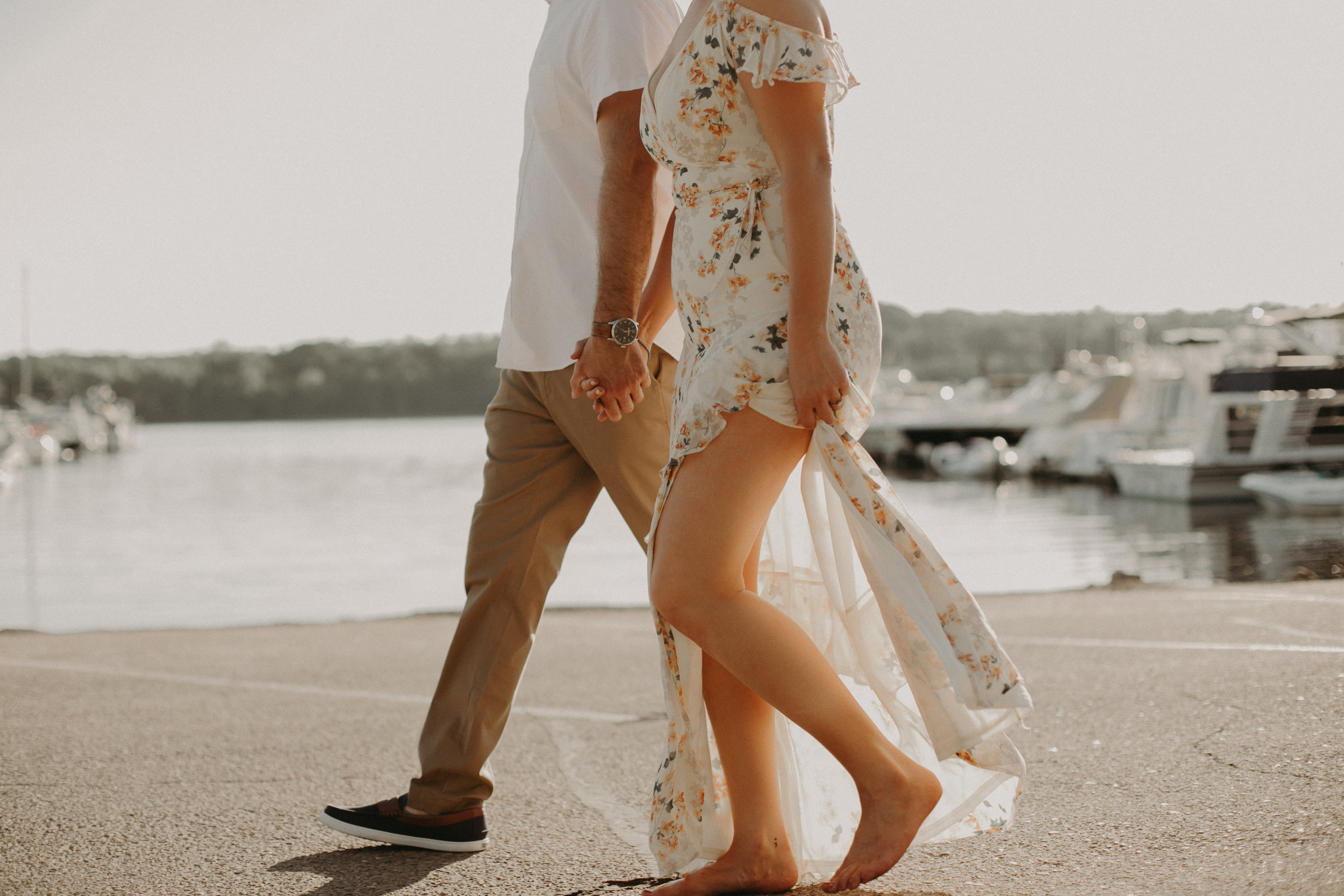 a couple strolls holding hands at the St Croix Marina during an engagement session with Andrea Wagner Photography