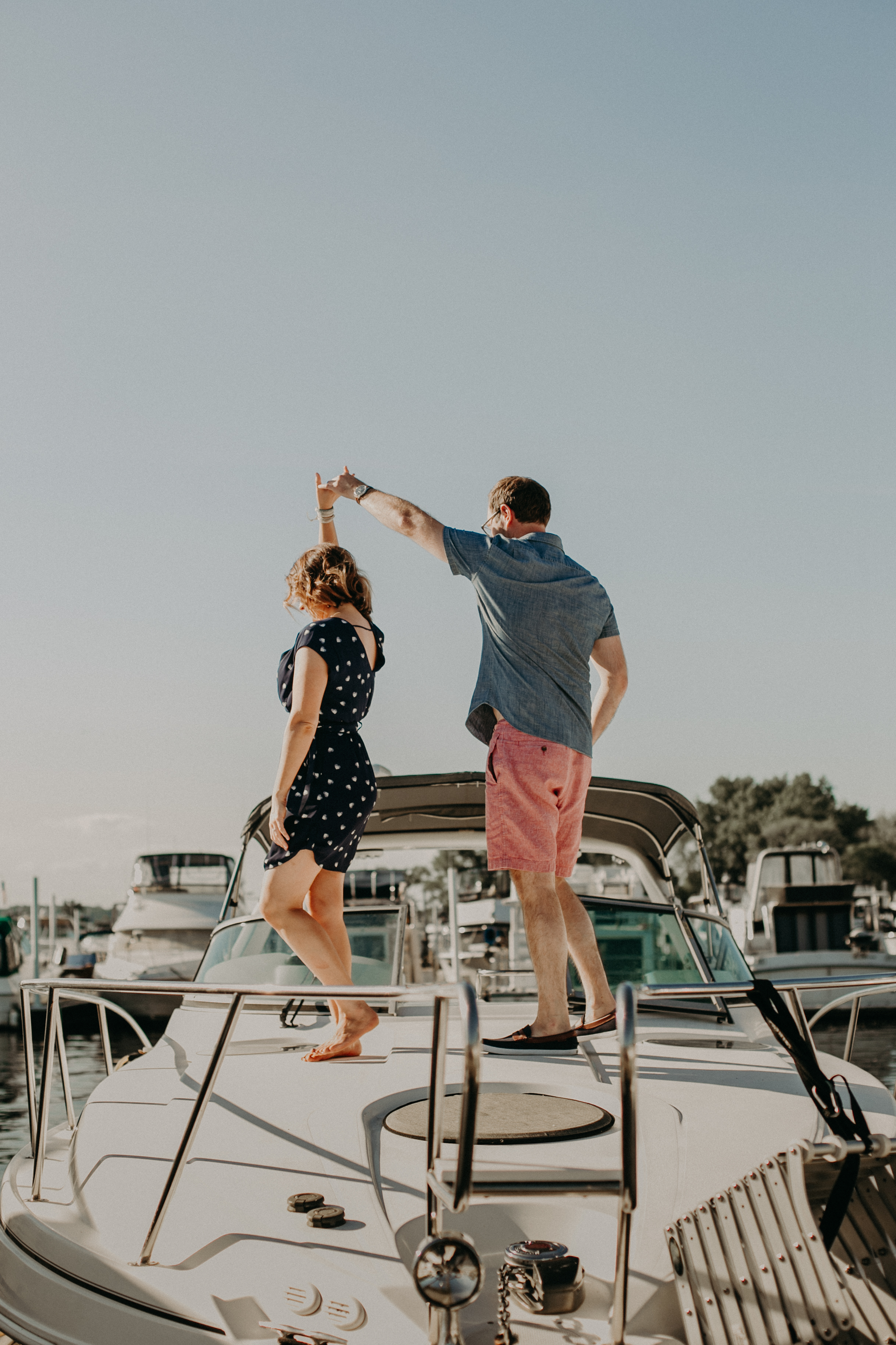 a couple dances during their engagement session on top of their boat located in Hudson WI in the St Croix Marina