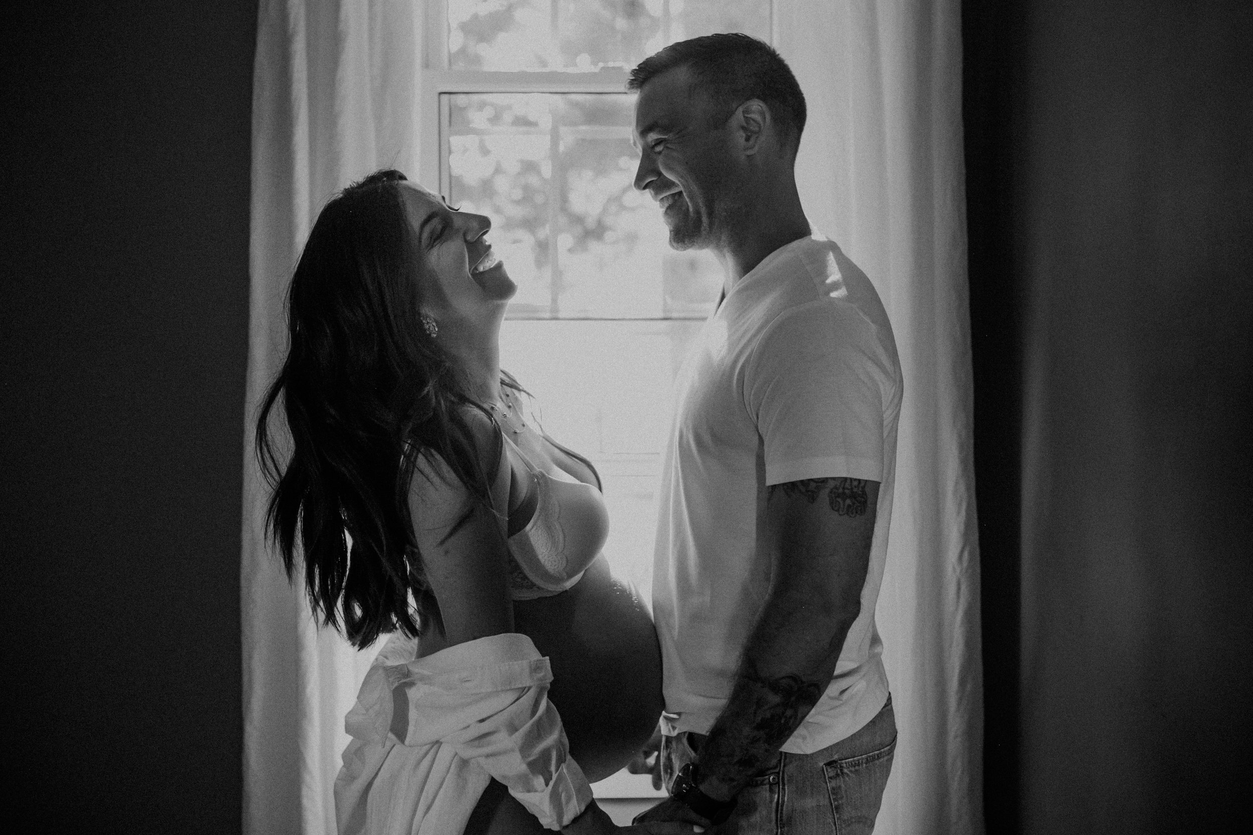 a cozy and intimate black and white image of woman pregnant with her partner during maternity photos