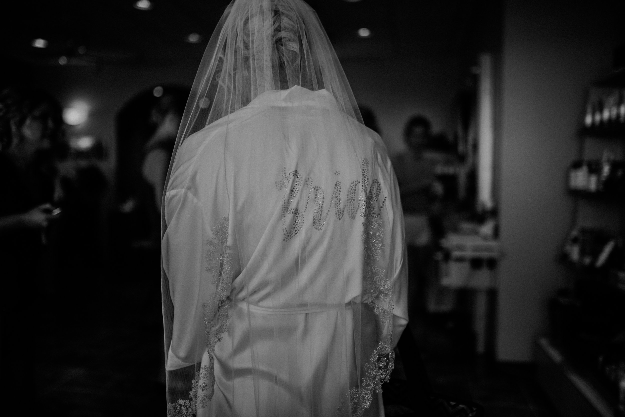 moody black and white photo of a bride in Marshfield WI getting ready at Blues Hair Studio
