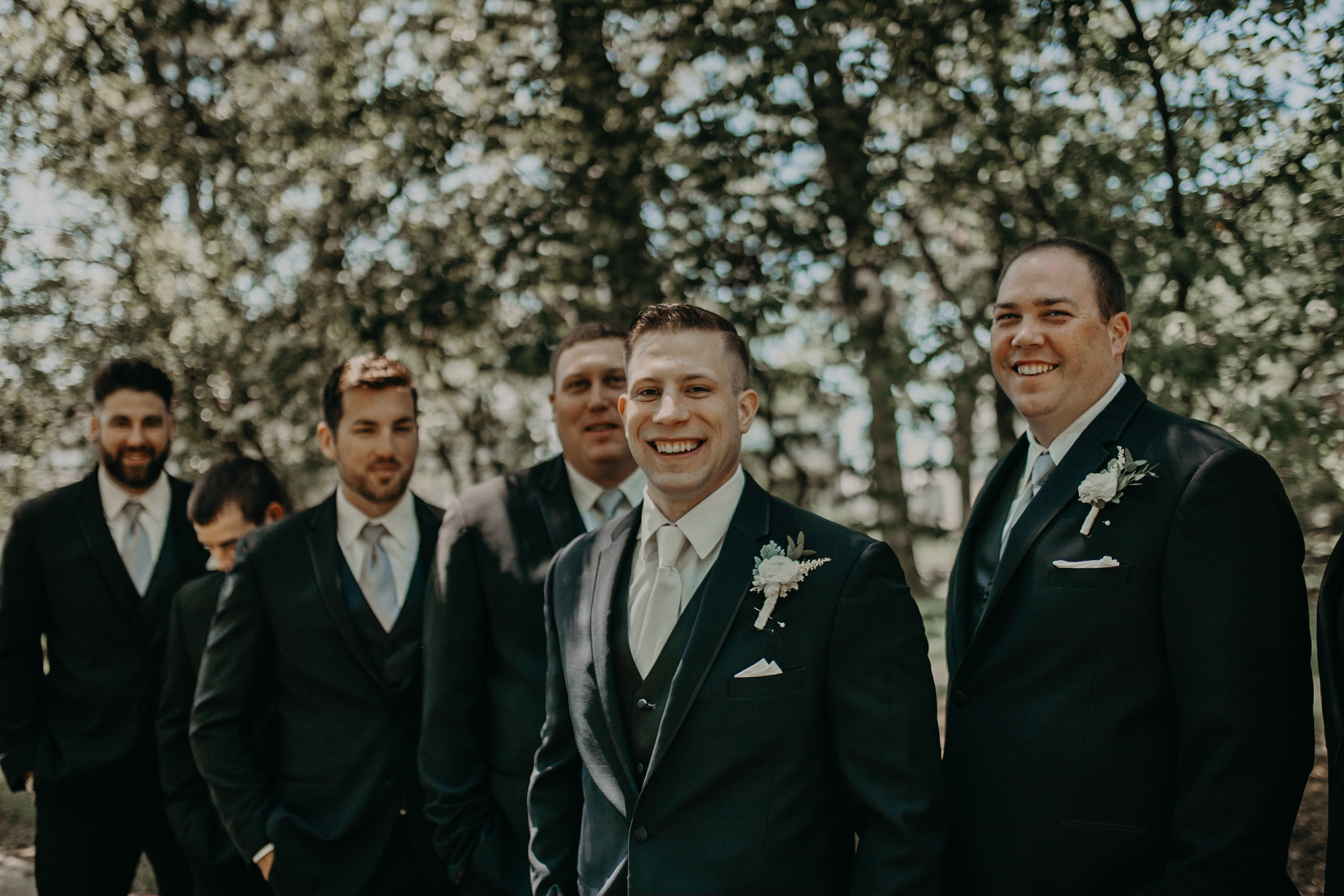 groom and his boys smile for group photos during his wedding at St Johns in Marshfield WI