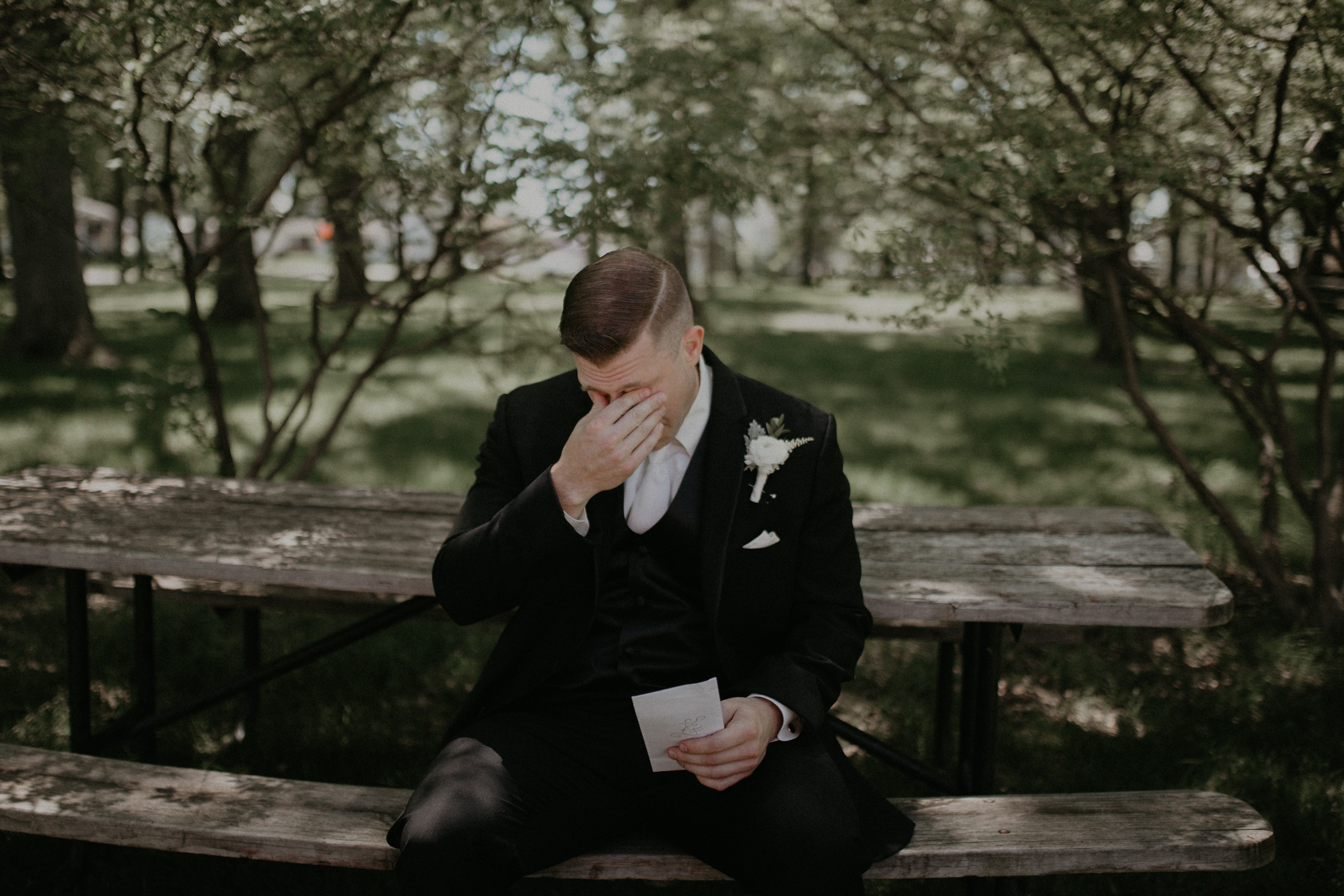 Marshfield WI groom cries while reading a love letter from his bride and is photographed by wedding photographer Andrea Wagner