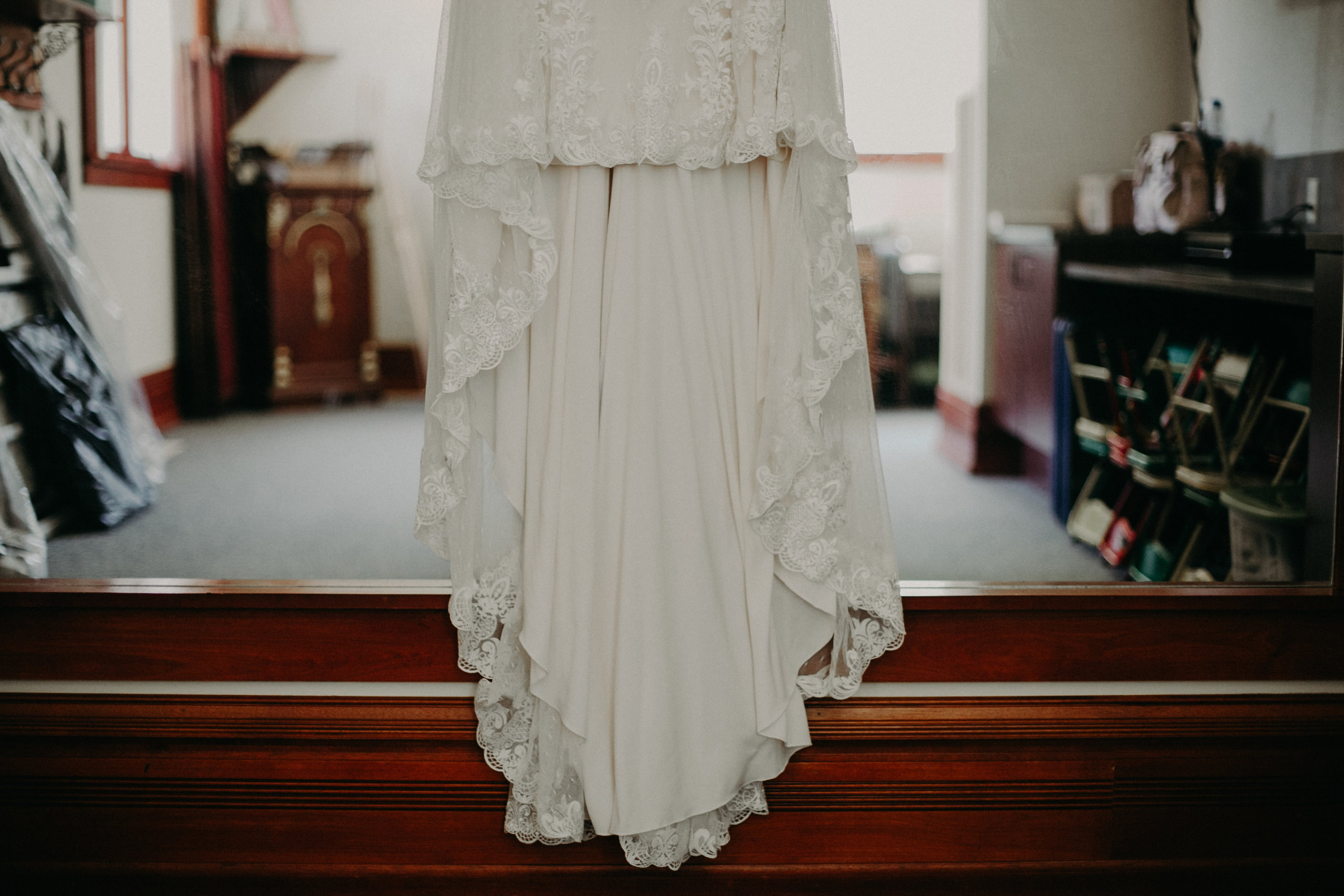 Justin Alexander lace wedding dress hanging in St Johns Catholic Church in Marshfield WI wedding by Andrea Wagner