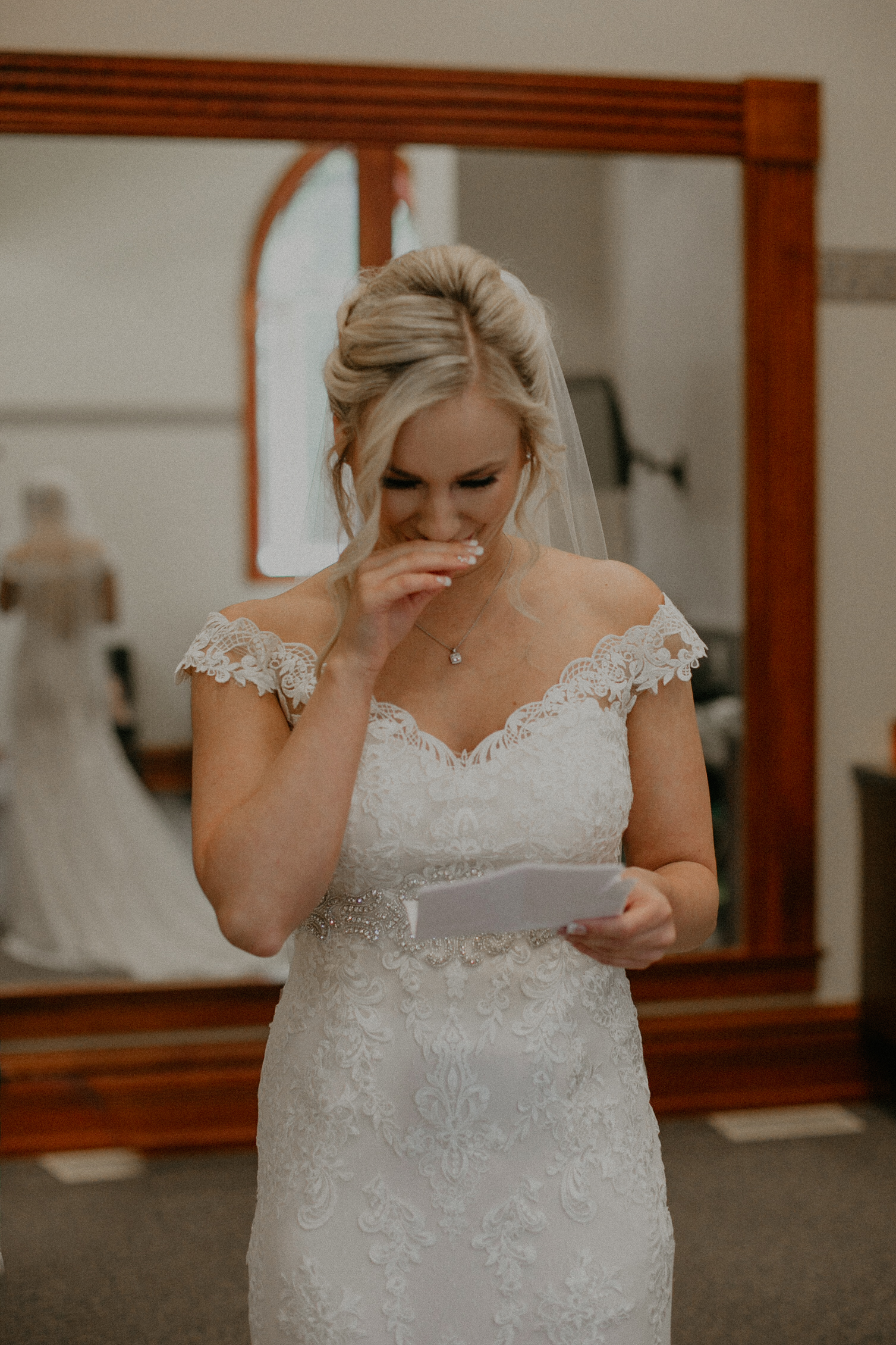 Bride cries while reading a love letter from her groom while Andrea Wagner captures real and authentic moments