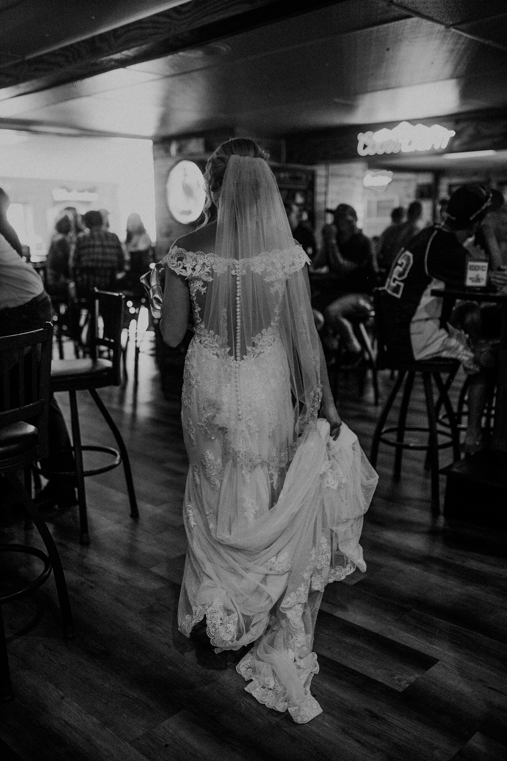 bride walks through a Marshfield bar Nutz Deep II while photographed by Andrea Wagner