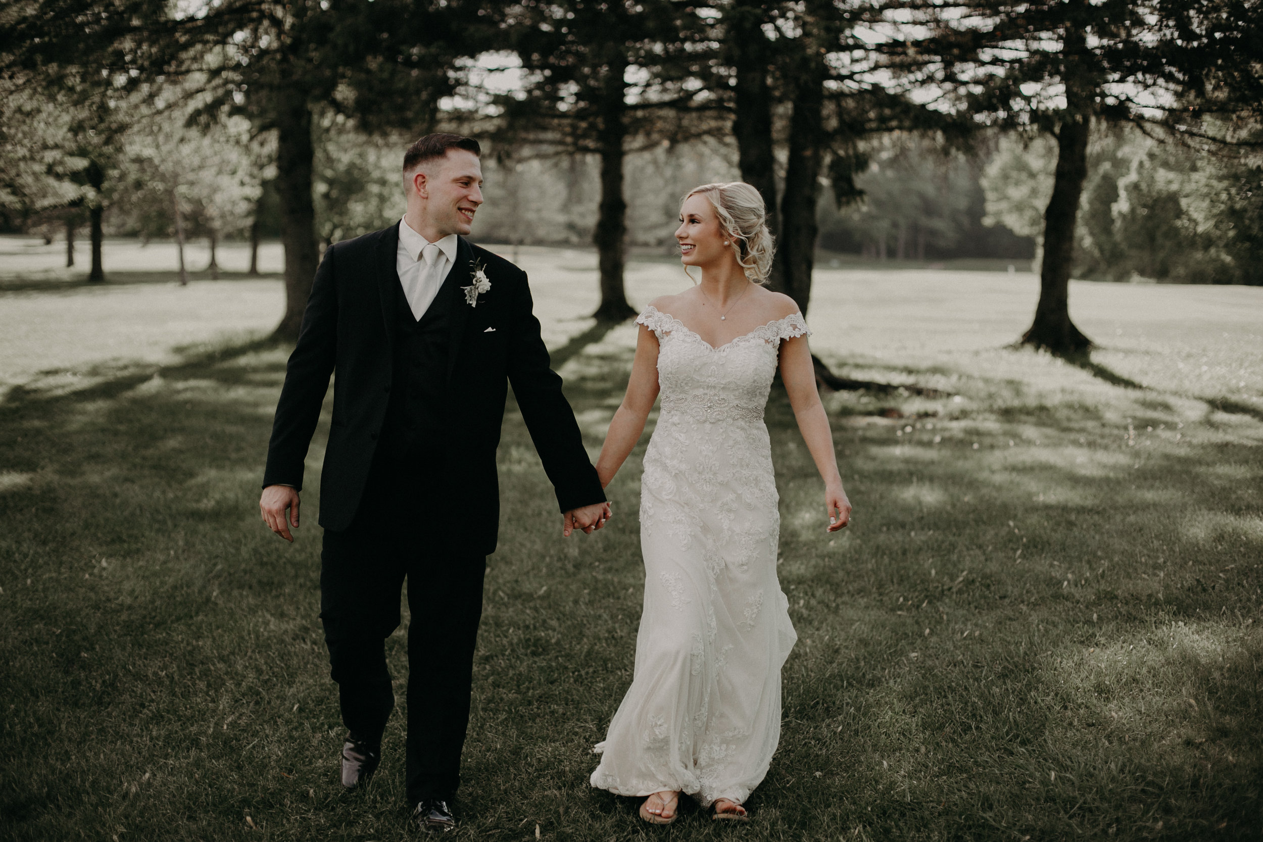 bride and groom portraits walking on the grounds at River Edge Golf Club in Marshfield WI