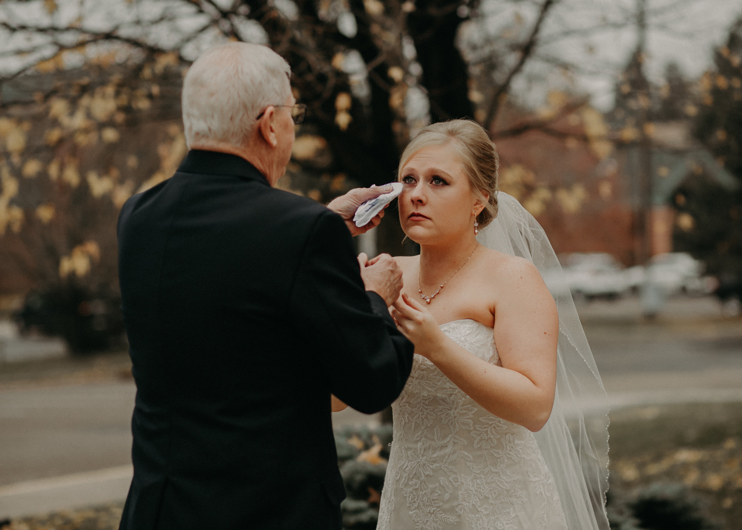 bride becomes emotional as her grandfather wipes her cheek after a first look on her wedding day at St Bridget's Catholic Church in River Falls WI