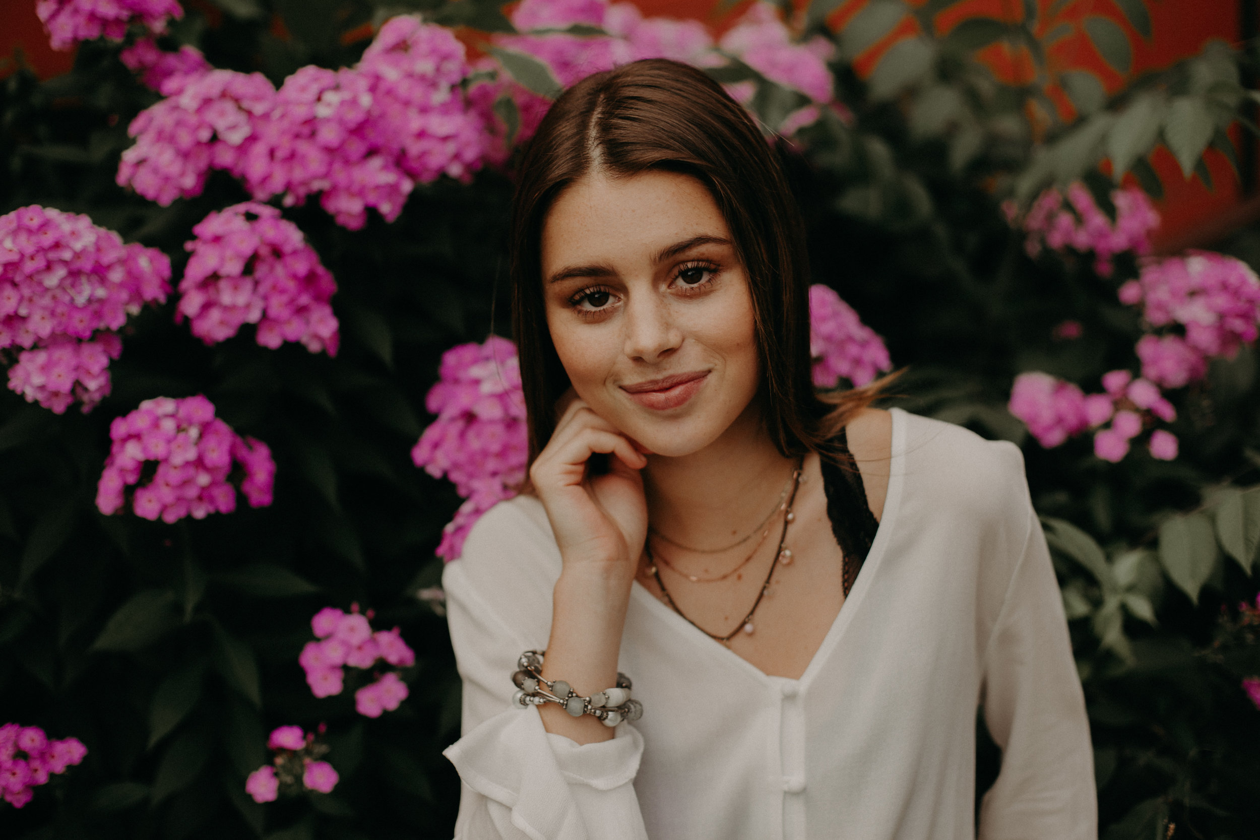 Andrea Wagner Photography captures colorful pink flowers in the background of a high school senior's photos in Stillwater MN
