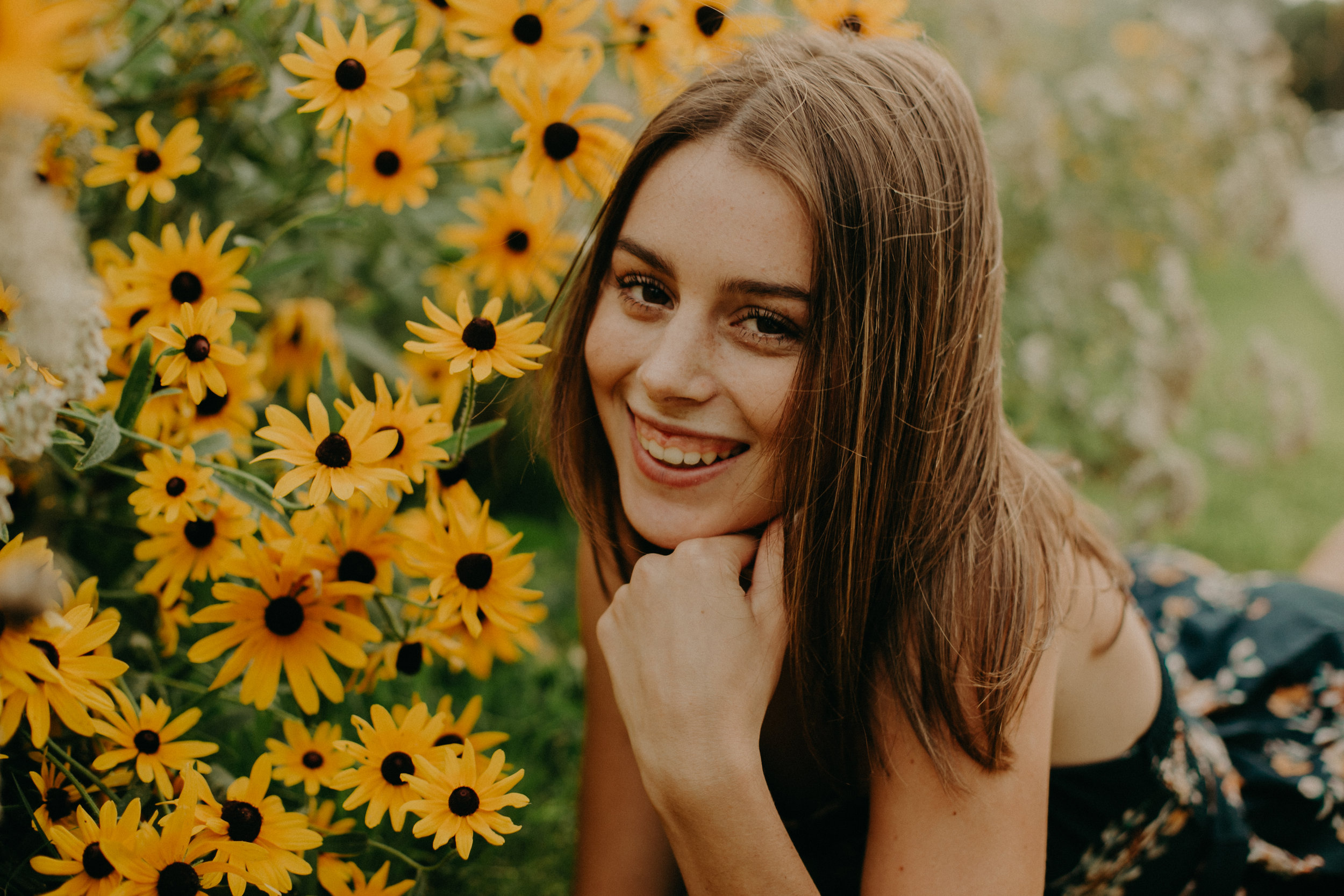 Andrea Wagner Photography makes senior laugh during senior photos in daisy field in Stillwater MN