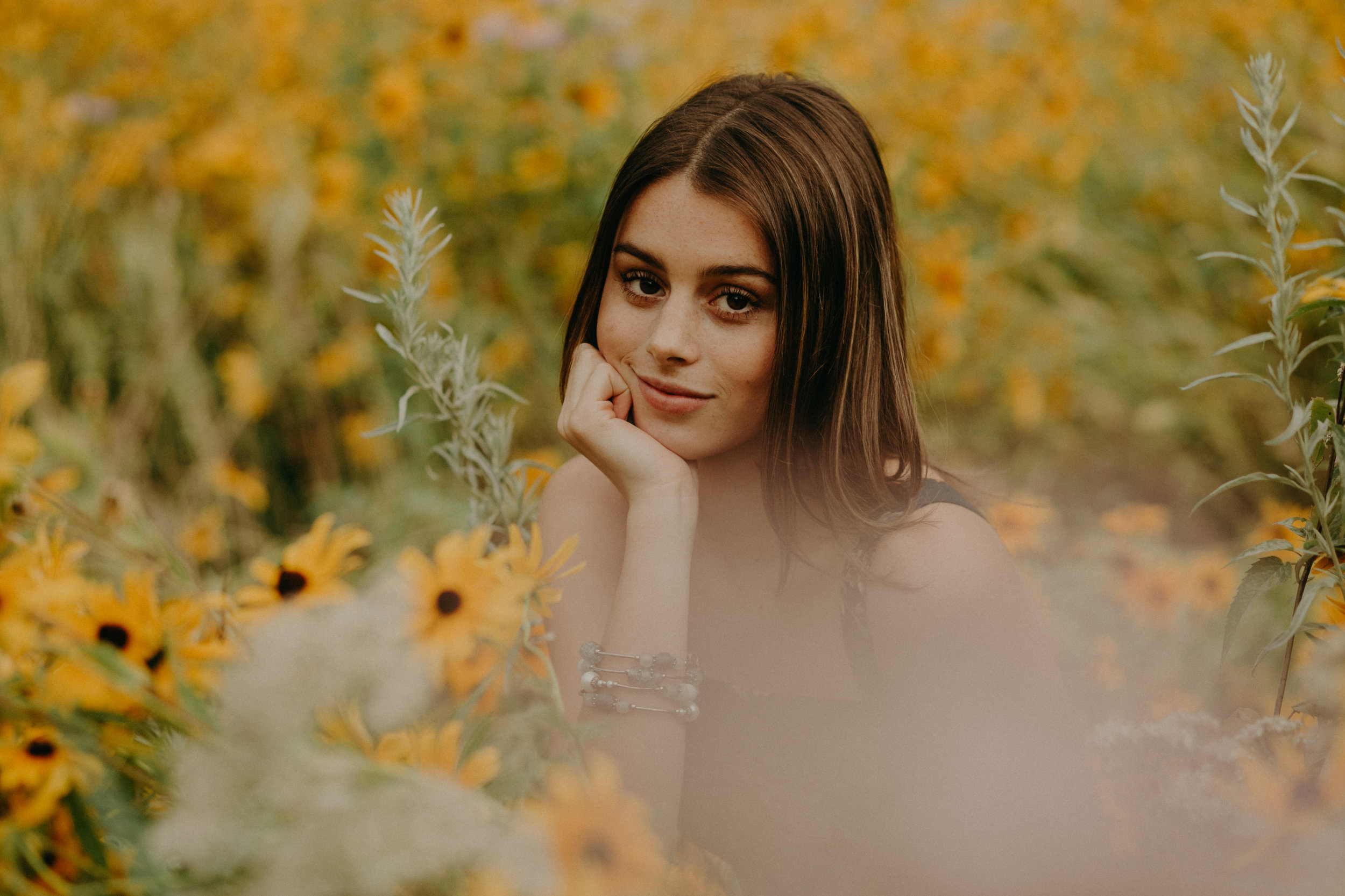 gorgeous high school senior sits in a field of yellow daisies in Minneapolis MN