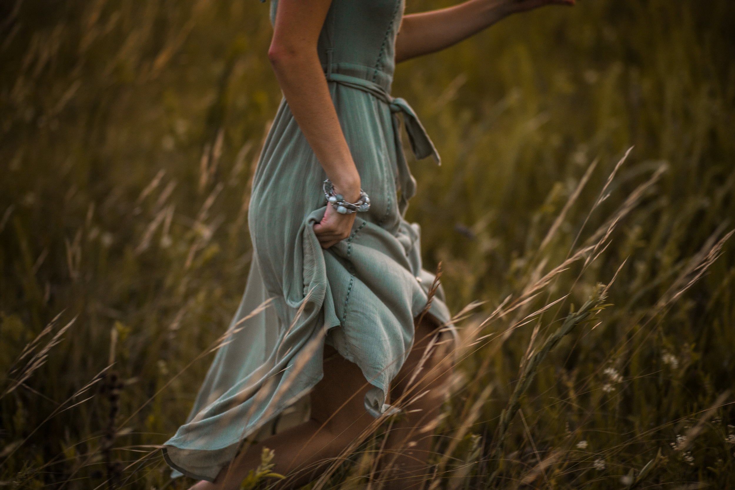 Hudson High School senior runs through a meadow during her photo session with Andrea Wagner in Stillwater MN