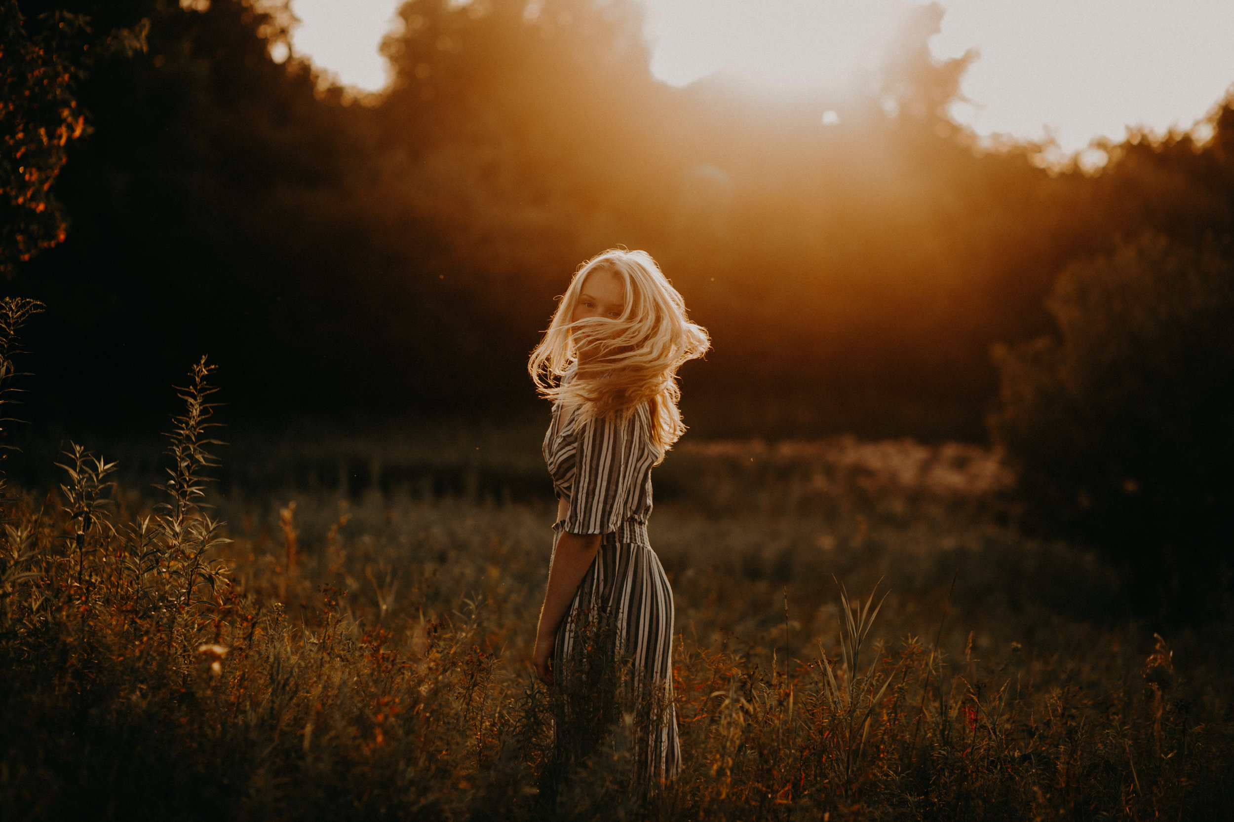 incredible sunset with golden light in a field while high school senior from Spooner WI whips her hair to look at photography Andrea Wagner