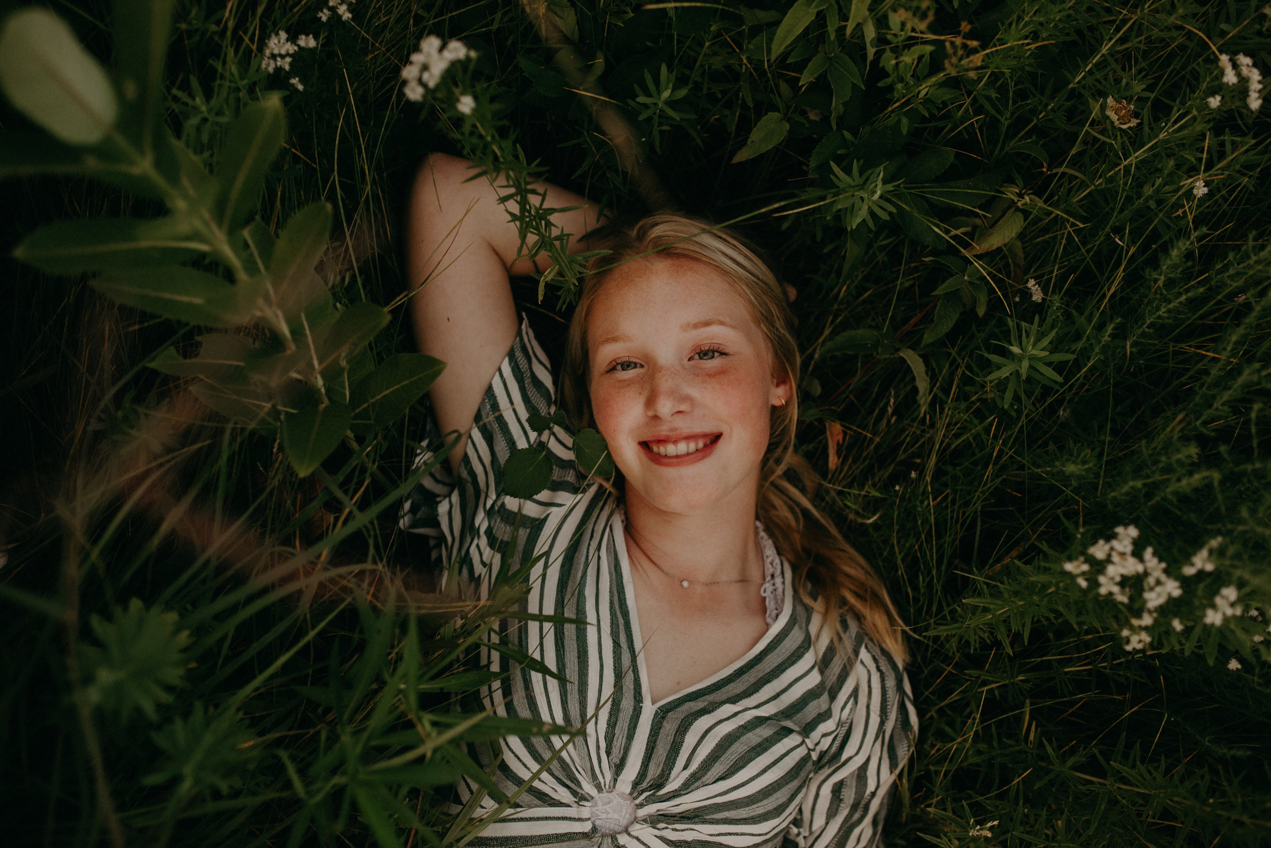 epic shot of a woman laying in a flower field smiling at the camera during her senior photos in Hudson WI