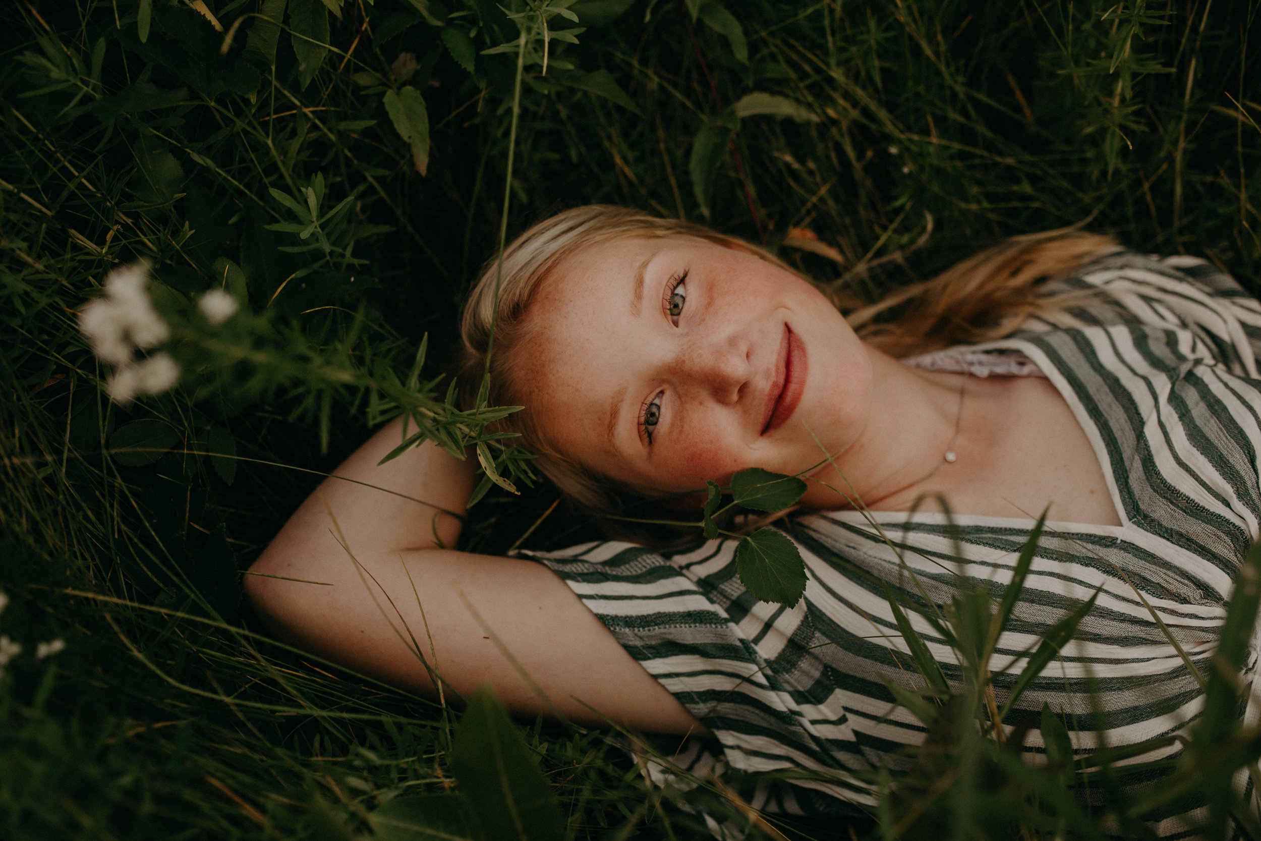 woman laying in a flower field in Hudson WI during senior photo shoot
