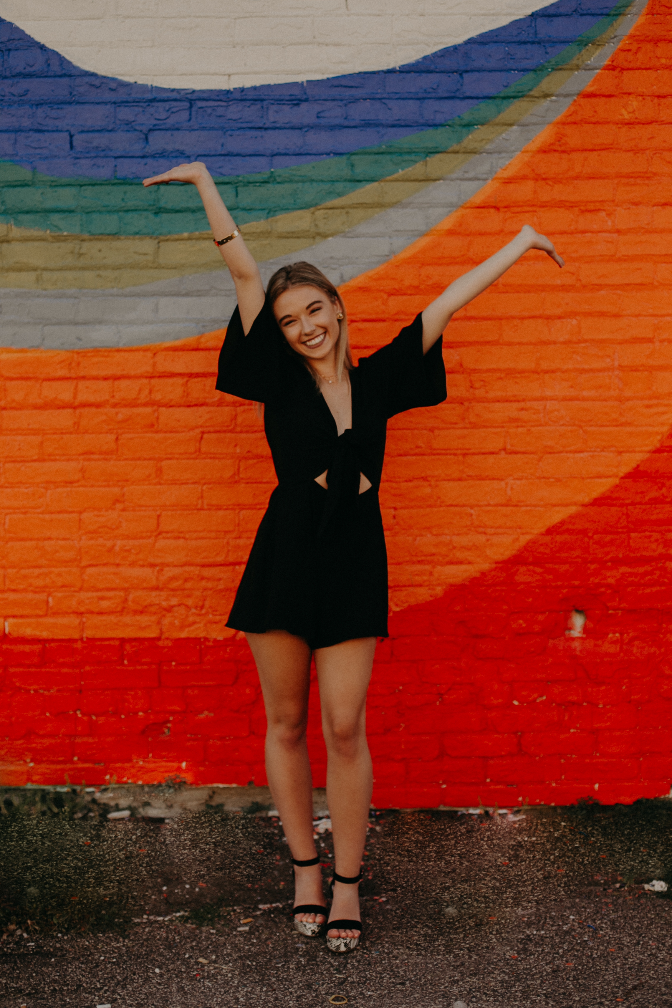 colorful brick mural wall in downtown Minneapolis makes great backdrop for senior photos by Andrea Wagner Photography