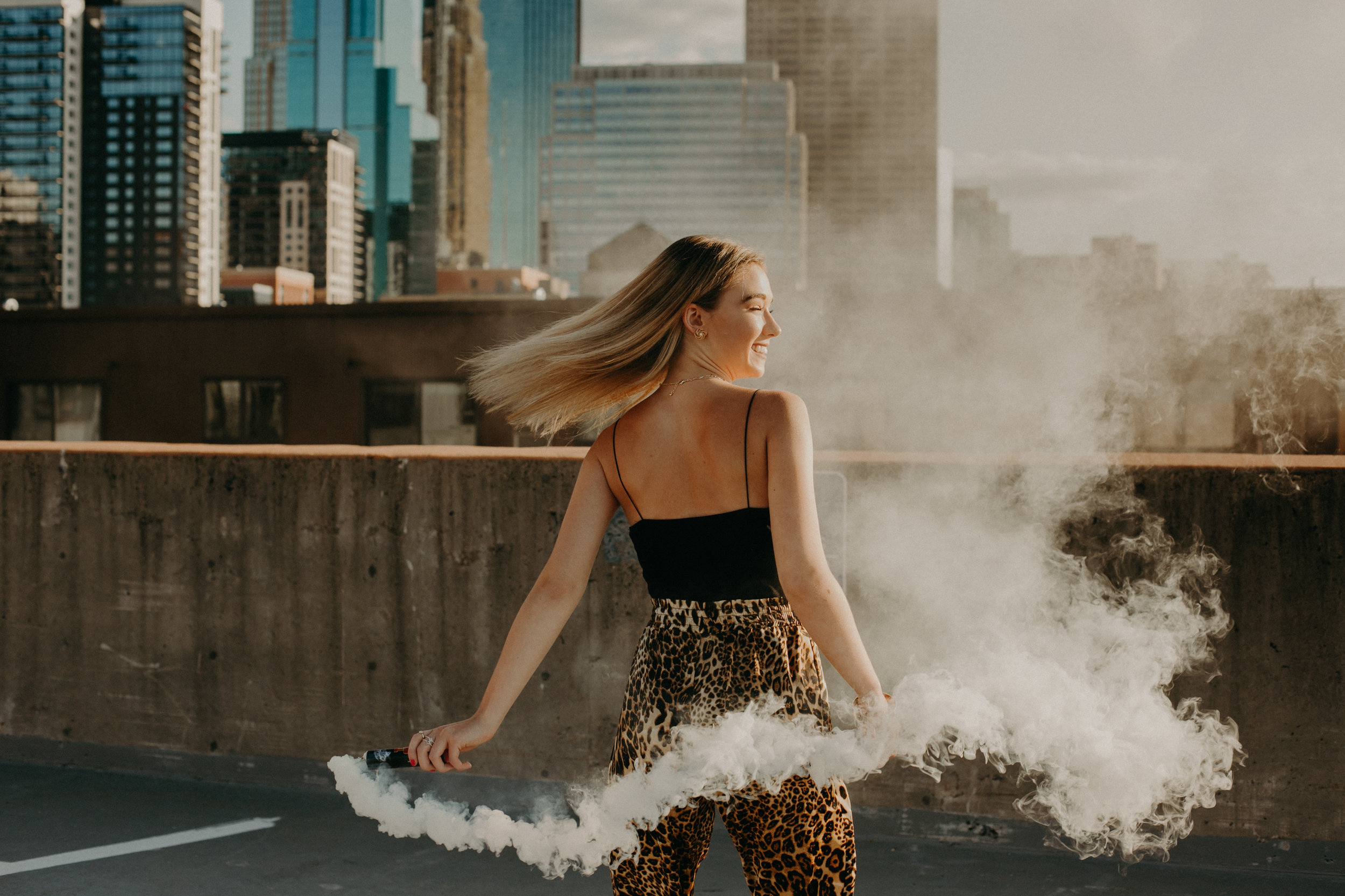 high school senior in Minneapolis MN wearing leopard pants and white smoke bombs during senior photoshoot with Andrea Wagner Photography