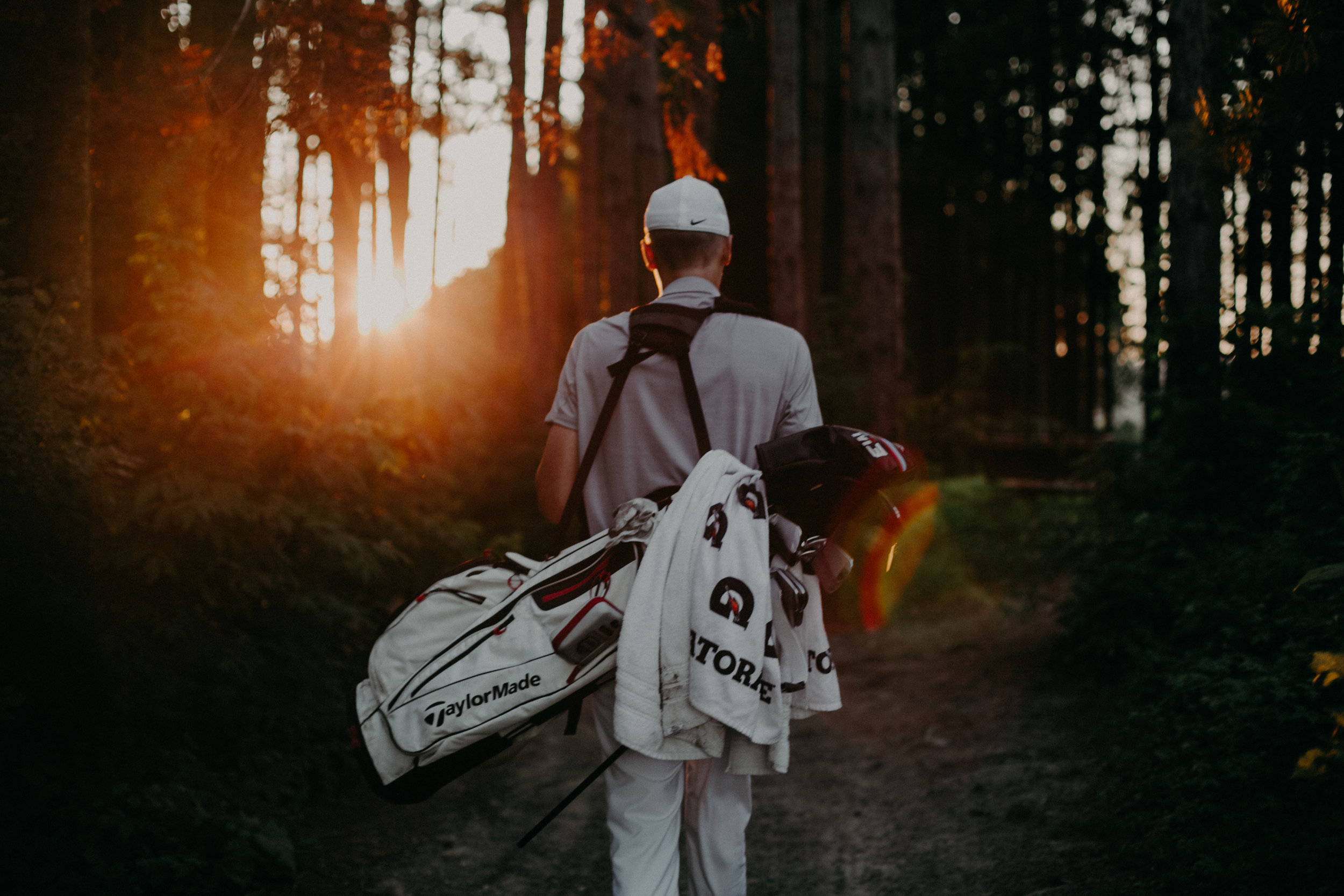 golfer carrying his clubs during sunset photo session at Spring Valley Golf Club in Wisconsin