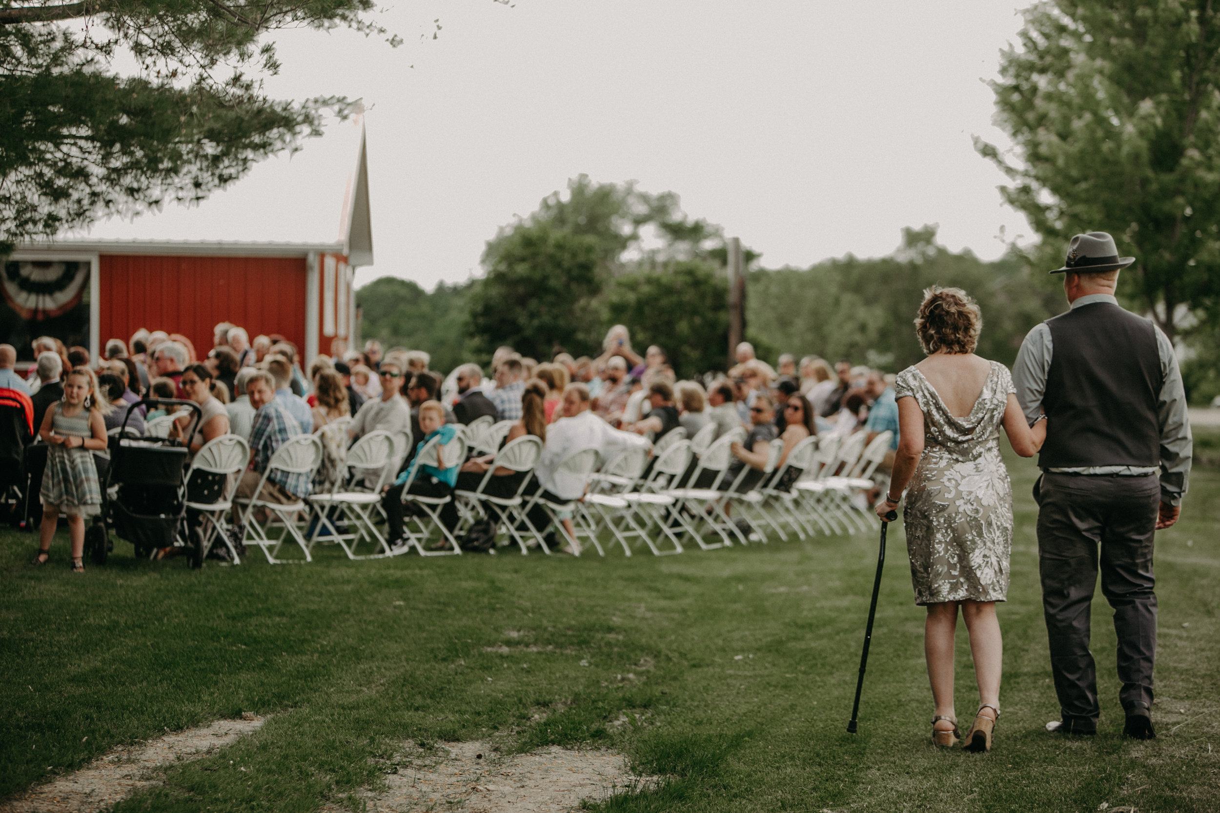 Ellsworth WI wedding photographer Andrea Wagner captures a moment where the groom walks his mother down the aisle at Jean Acres Barn