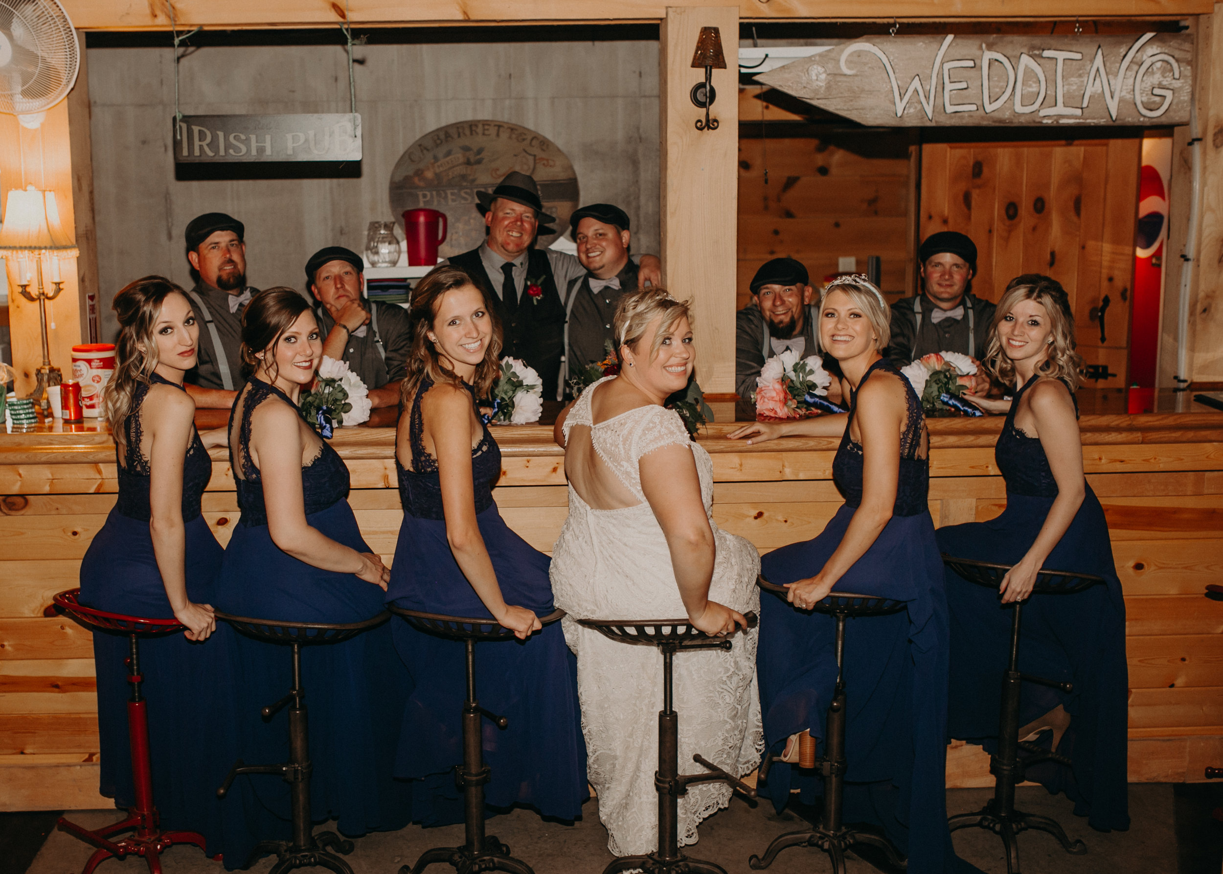 bridal party poses for a photo at the bar at Jean Acres in Ellsworth WI captured by Andrea Wagner Photography