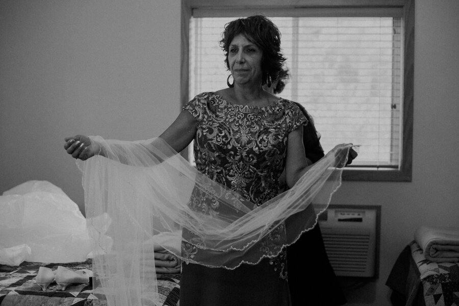 moody black and white image of bride getting ready at Pine Lake Camp in Waupaca WI