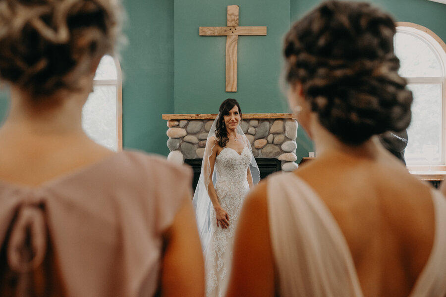 a bride reveals herself and dress to her bridesmaids in Waupaca WI at Pine Lake Resort