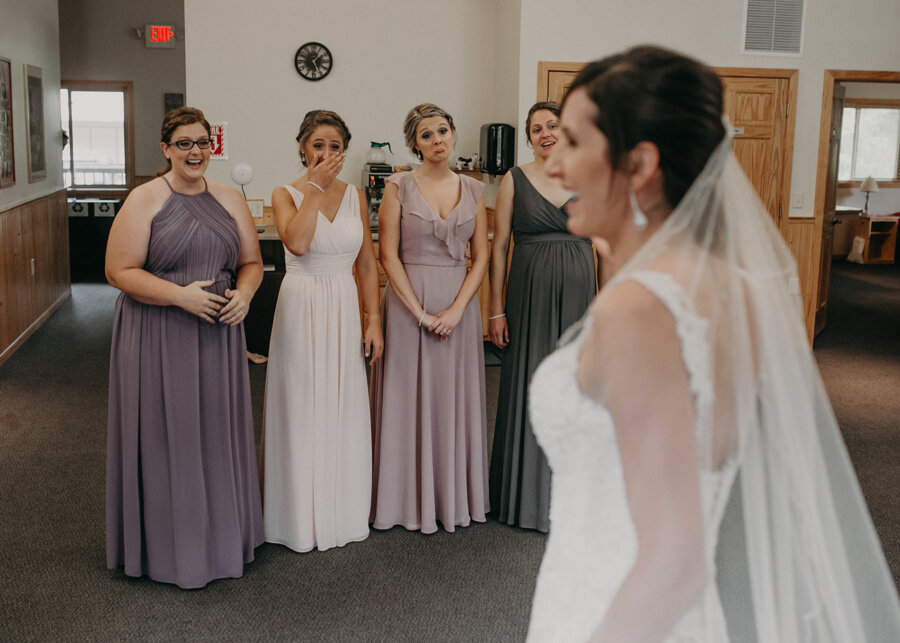 emotional moment when bride reveals her dress to her bridesmaids at Pine Lake Resort in Waupaca WI
