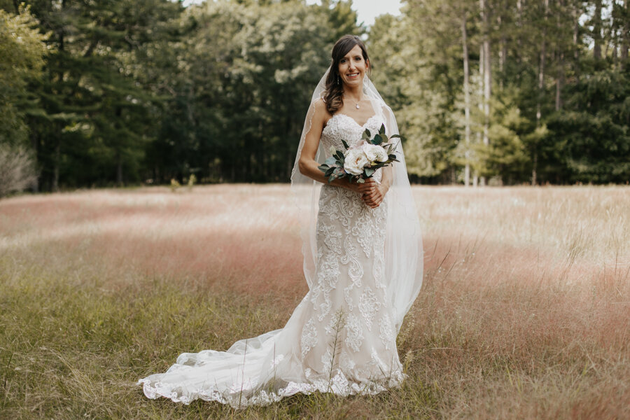 beautiful bridal portraits in a pink field at Pine Lake Resort in Waupaca WI