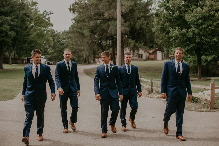 groom and groomsmen walk along the grounds of Waupaca wedding venue Pine Lake Camp