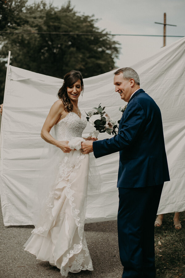 Andrea Wagner Photography captures father of the bride helping his daughter before her wedding at Pine Lake Camp in Waupaca WI
