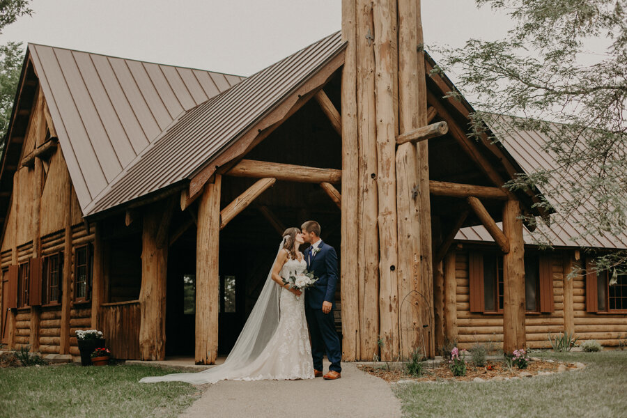 bride and groom pose in front of the chapel at Pine Lake Resort in Waupaca WI