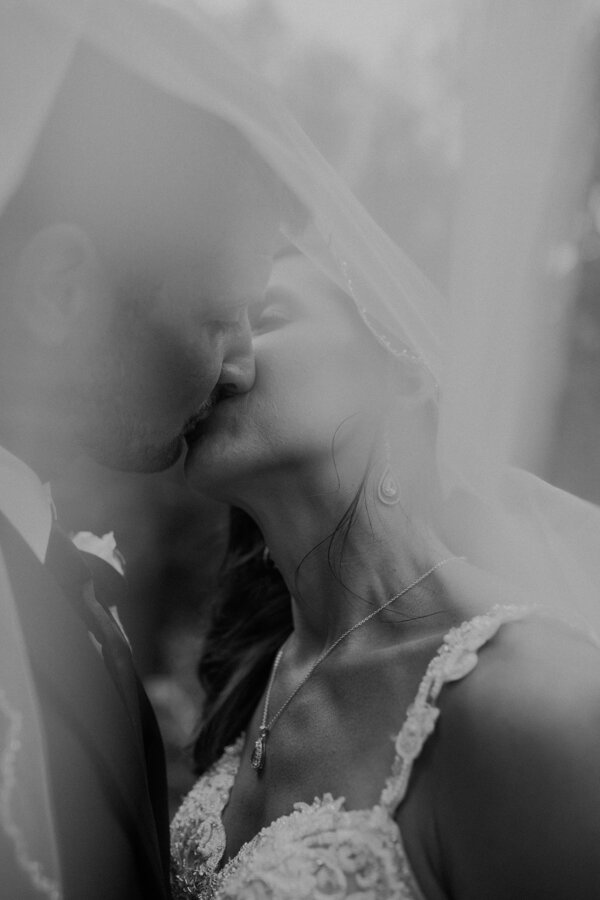 black and white photo of Waupaca bride and groom kissing under her veil by Stella York