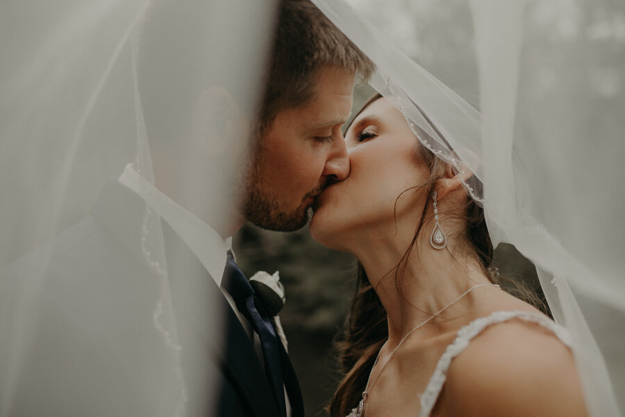wisconsin bride and groom kiss under veil at The Mill in Waupaca WI photographed by Andrea Wagner