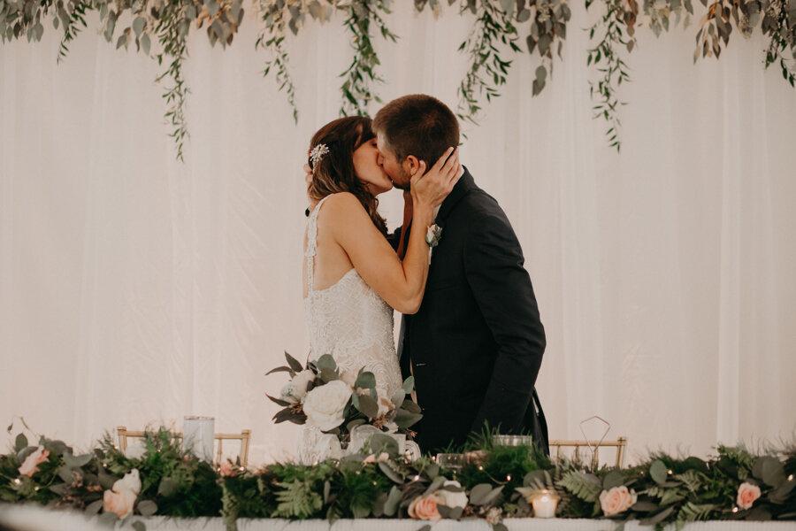 Waupaca wedding kiss between bride and groom during dinner at Par 4 Resort