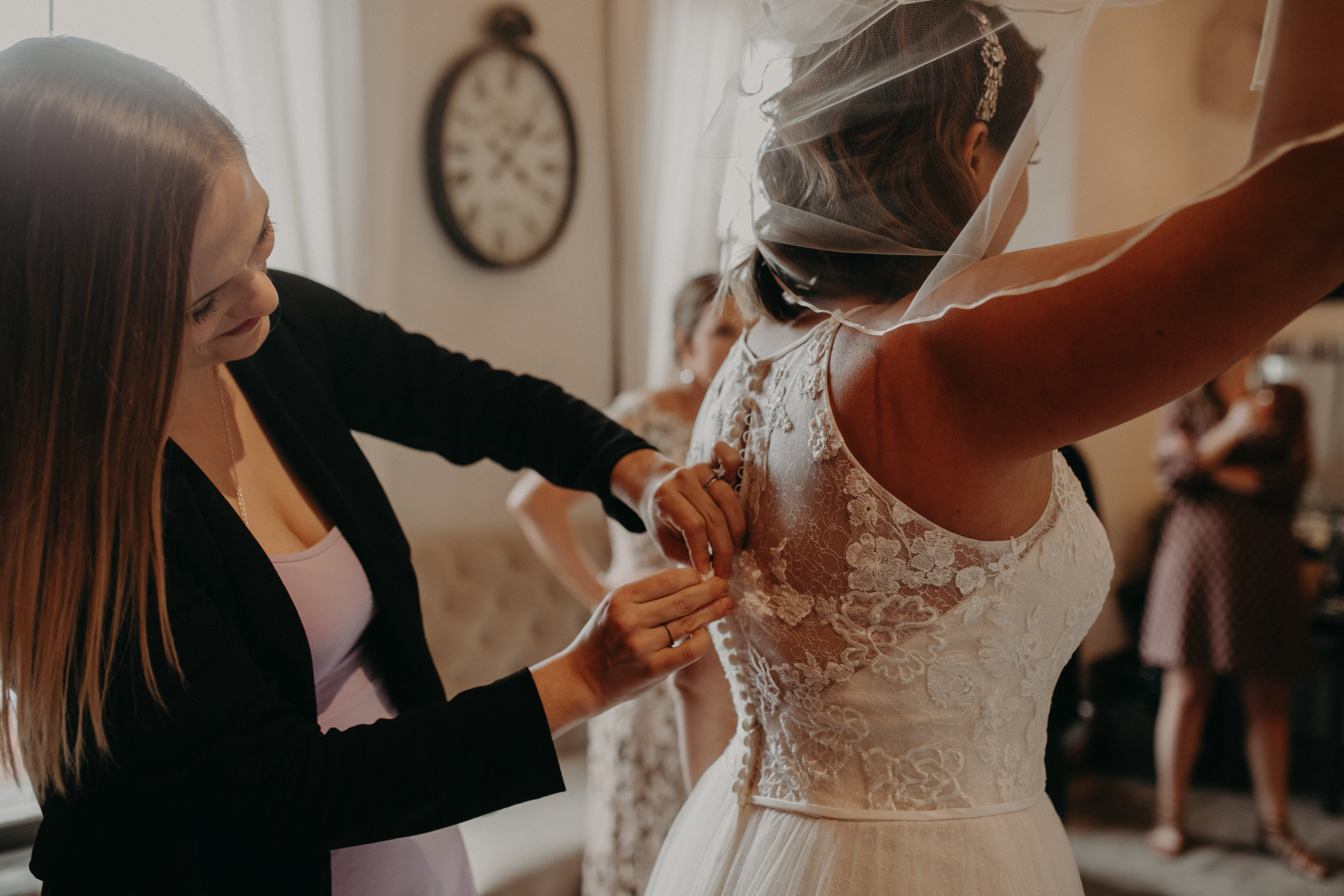 bride's sister helps her get into her wedding dress in the Loft at Studio J dressing room