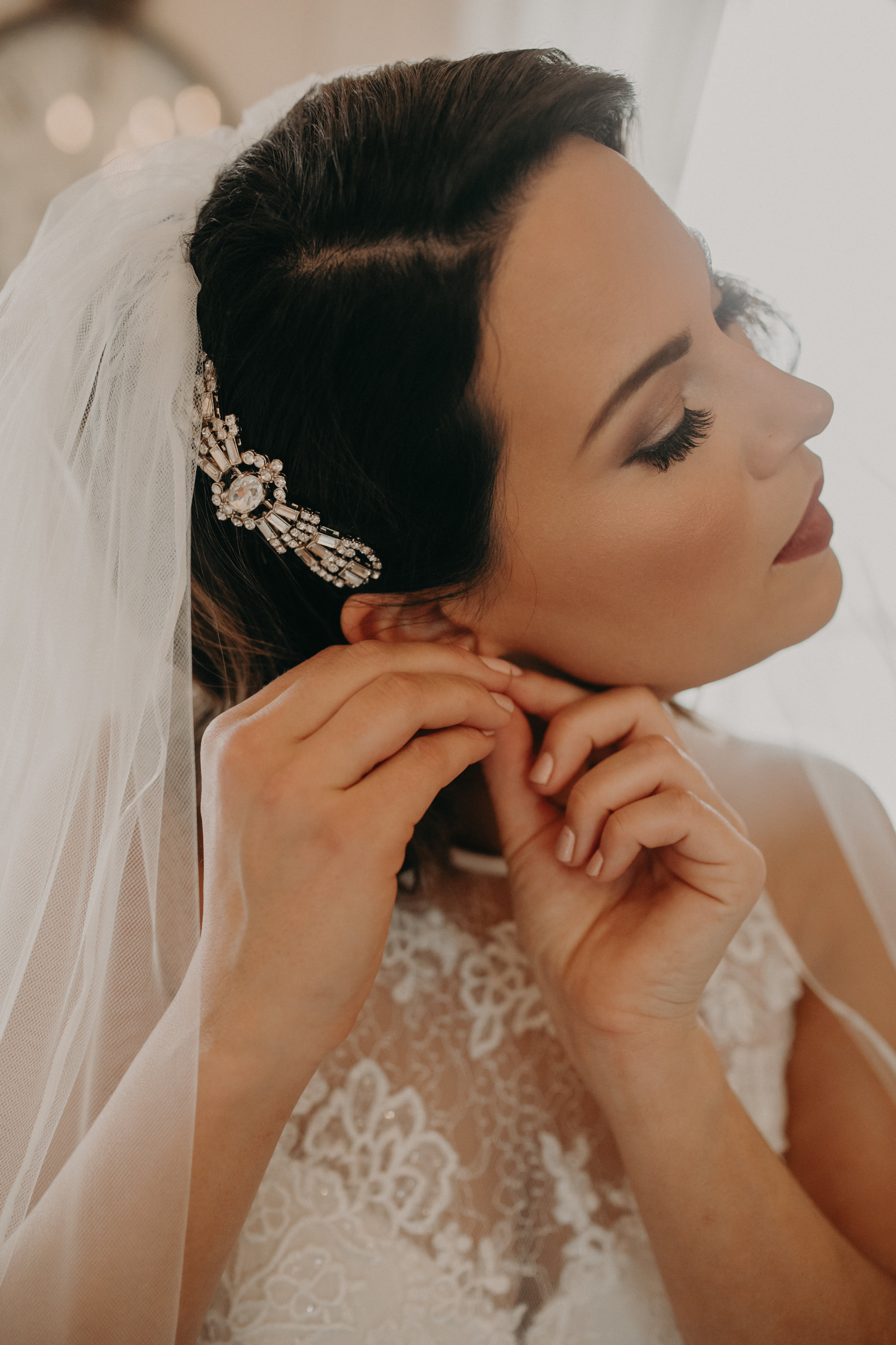 a bride puts on her earrings before her wedding in the getting ready space at The Loft at Studio J