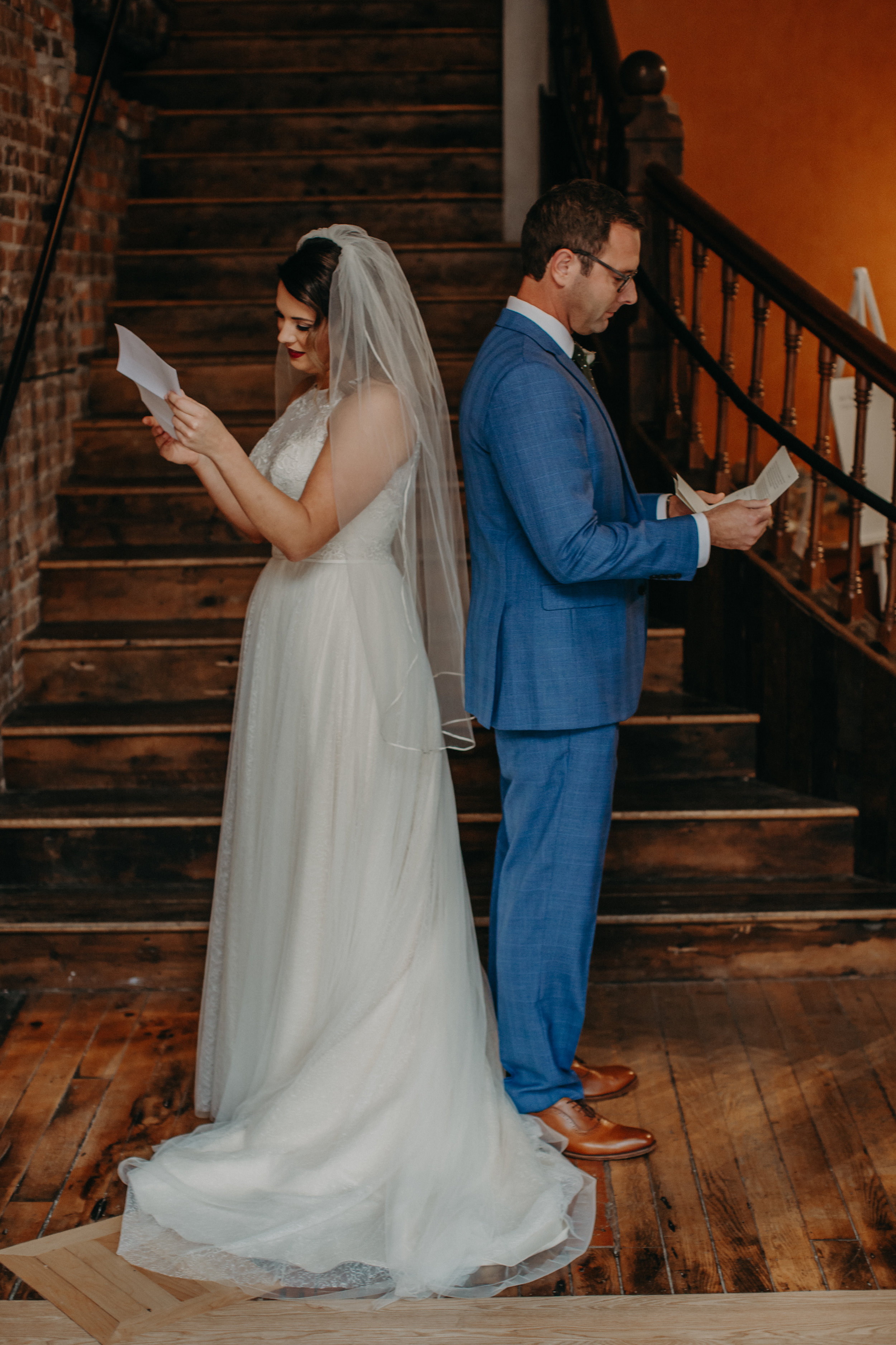 a Stillwater Mn bride and groom read intimate letters before their first look at The Loft at Studio J