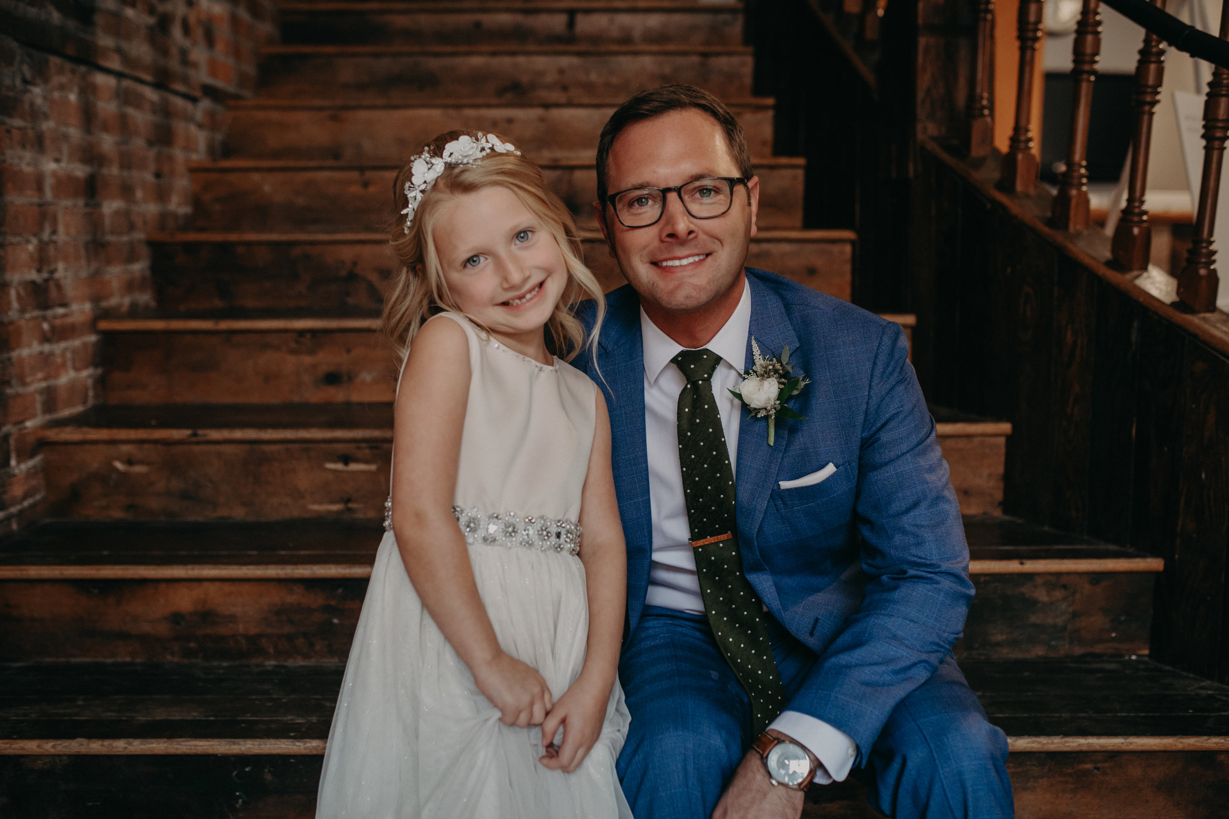 a groom wearing Brooks Brothers Milano suit hugs his daughter during his wedding at The Loft at Studio J in Stillwater MN