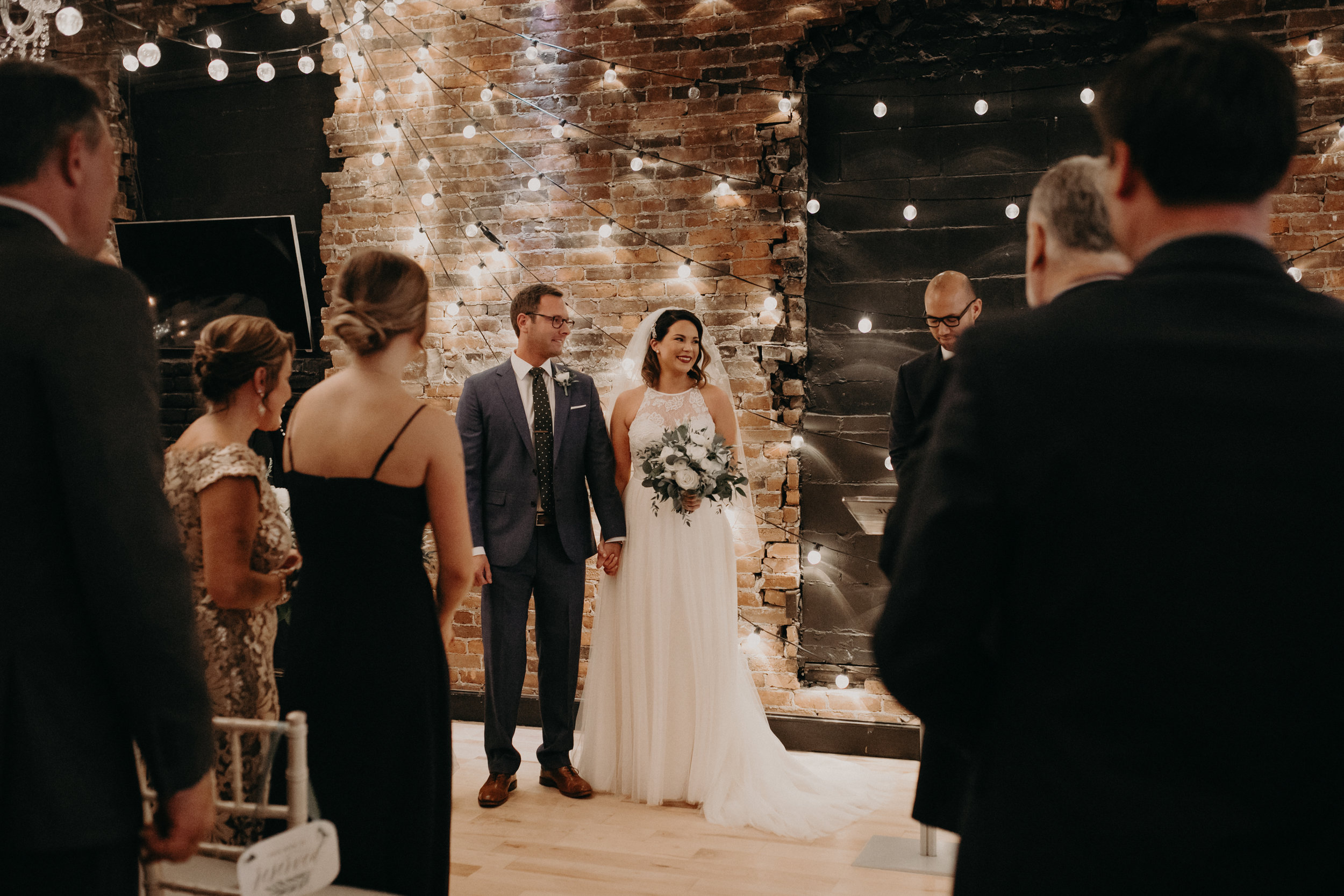 The Loft at Studio J has unique exposed brick backdrop and dim lighting for a wedding ceremony in Stillwater MN
