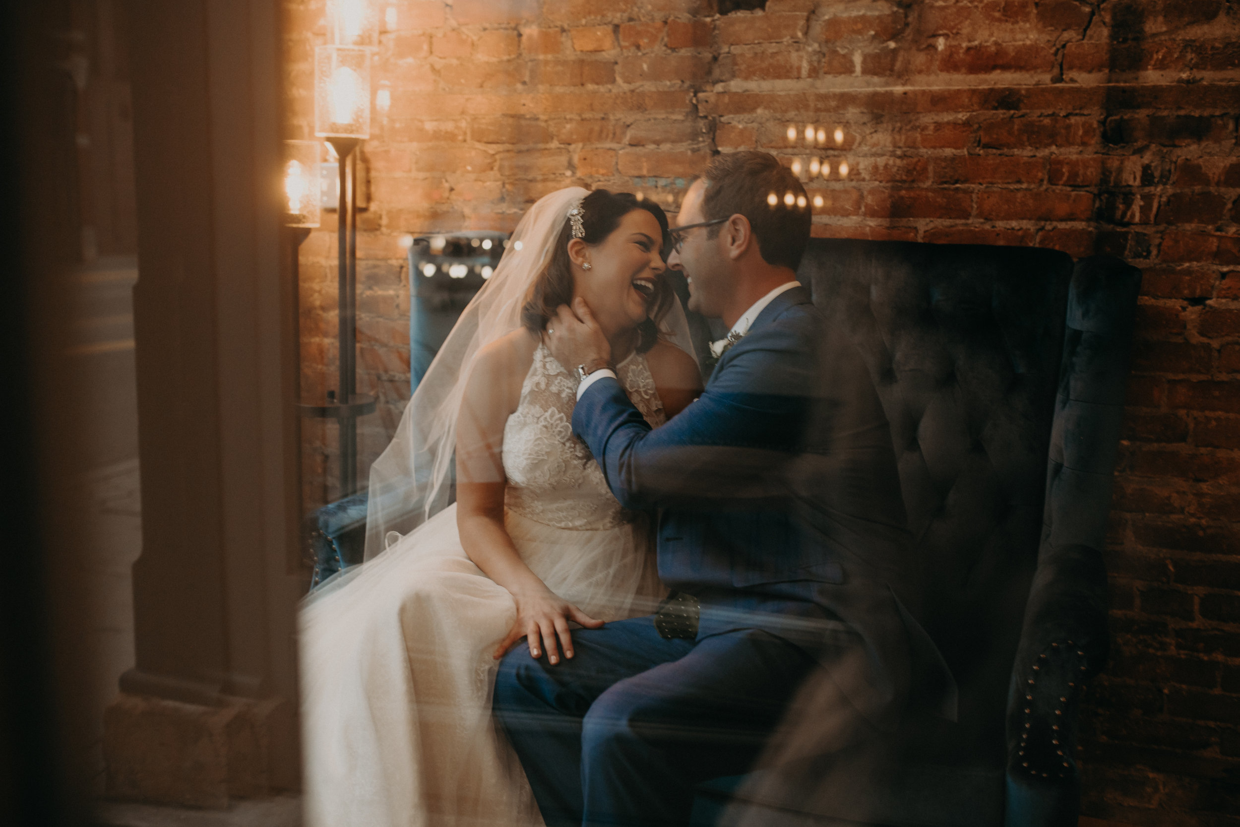bride and groom laugh and kiss in the window of The Loft at Studio J in Stillwater MN captured by AWP