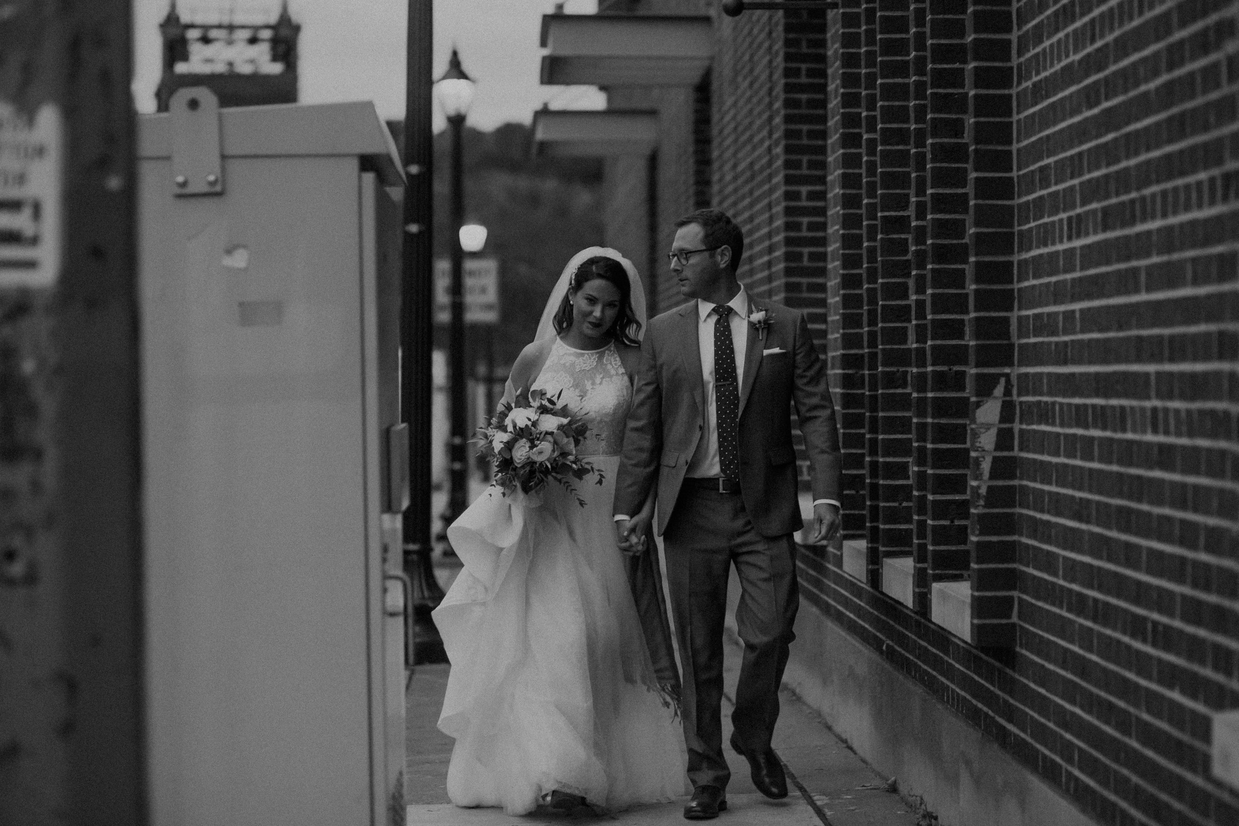 and bride and groom walk around the streets of Stillwater MN on their wedding day at sunset captured by Andrea Wagner Photography