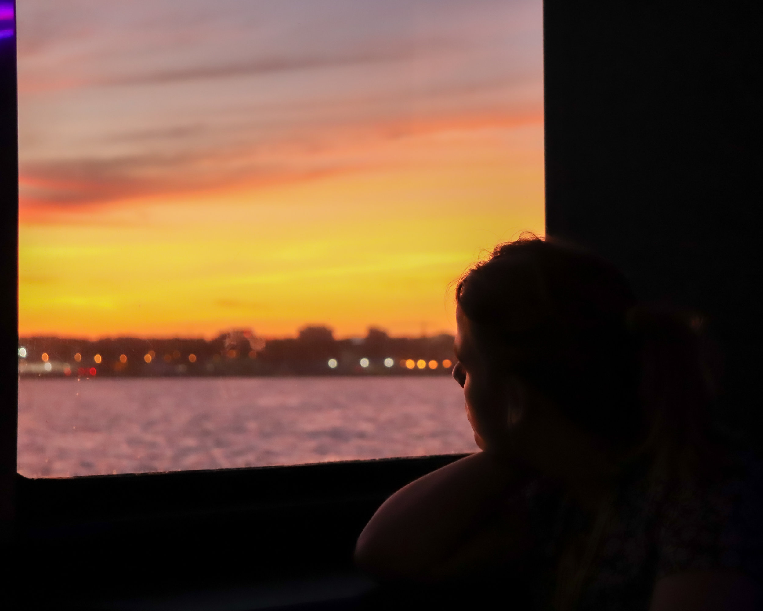 Madi, a residential assistant for the School of The New York Times, stares out the window of a cruise ship as it pulls into the harbour. Meanwhile, loud dance music blares throughout the cabin.