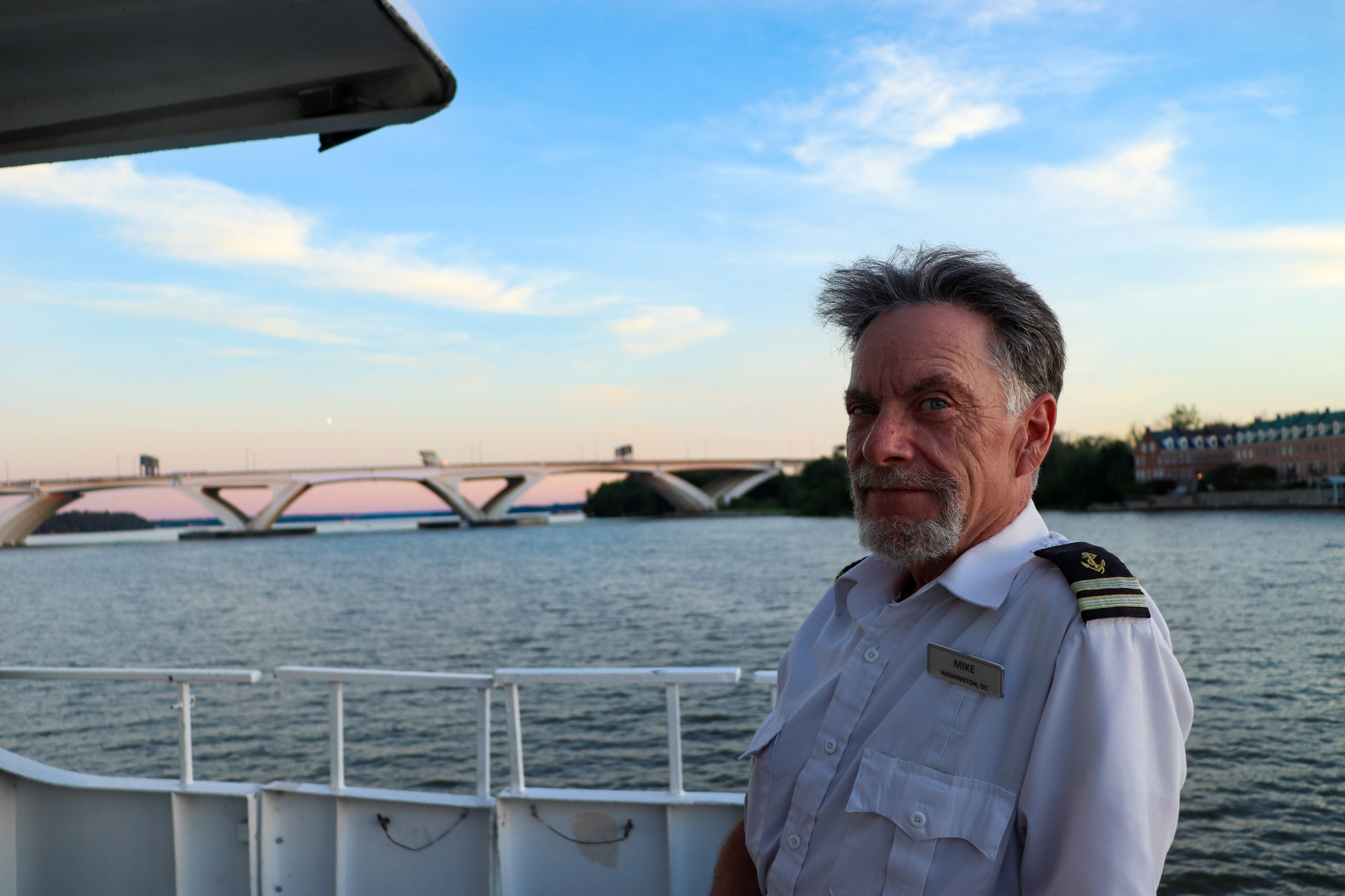"""Mike, an employee for a Potomac River cruise ship for the last six years, poses for a photo.   Q. """"Can you recall any of the most interesting days/moments of your job?""""  """"There's lots of little bits and fragments that you remember. You know, some nights you can see speckled stars across the sky accompanied by patches of cloud, with the moon glistening over the water, and it just makes for an amazing photograph ... I've never had any accidents or people falling into the water before, thank god. But one time we were pulling into the harbour with a group of kids, and something happened on the dance floor that caused someone to get injured. And I saw one kid crying and asked what was wrong, and he replied by saying, """"OH THE HUMANITY!"""" So I guess he really hadn't seen too many bad things in his life yet."""""""