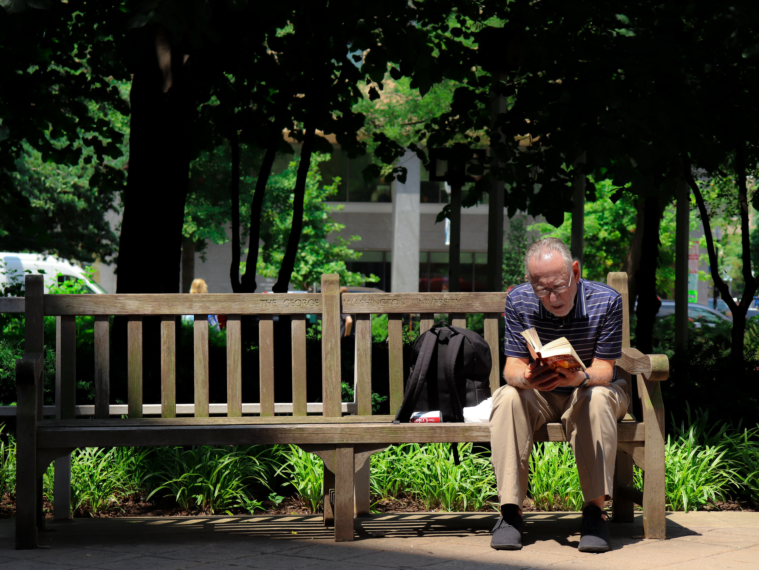 A man sits on a bench near the George Washington University Campus, deeply immersed in a Dan Simmons novel. Unable to remove his eyes from the page, he declined to comment.