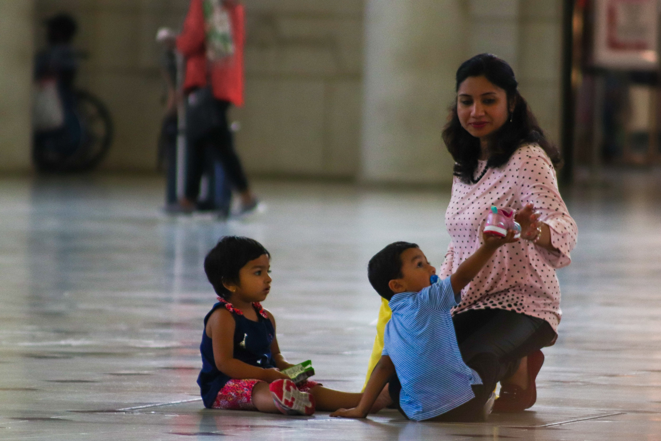 In the middle of Union Station, a mother helps to put on her daughter's shoe, which fell off during an intense game of tag with her brother.