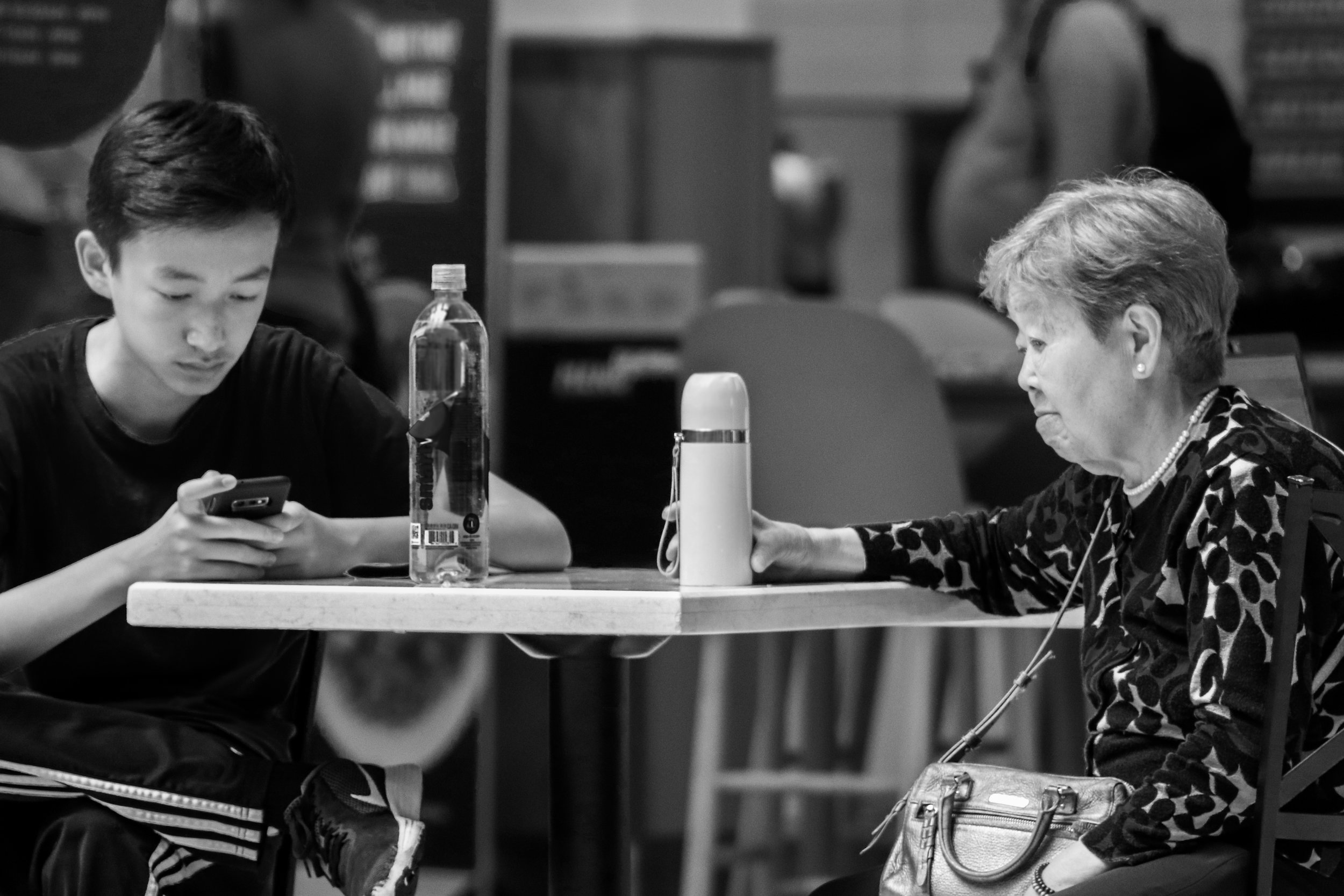 A grandmother and grandson sit together at the station's coffee shop. The grandson's eyes remain fixated on his phone while his grandmother gazes down at the floor, clutching onto her light pink water bottle.
