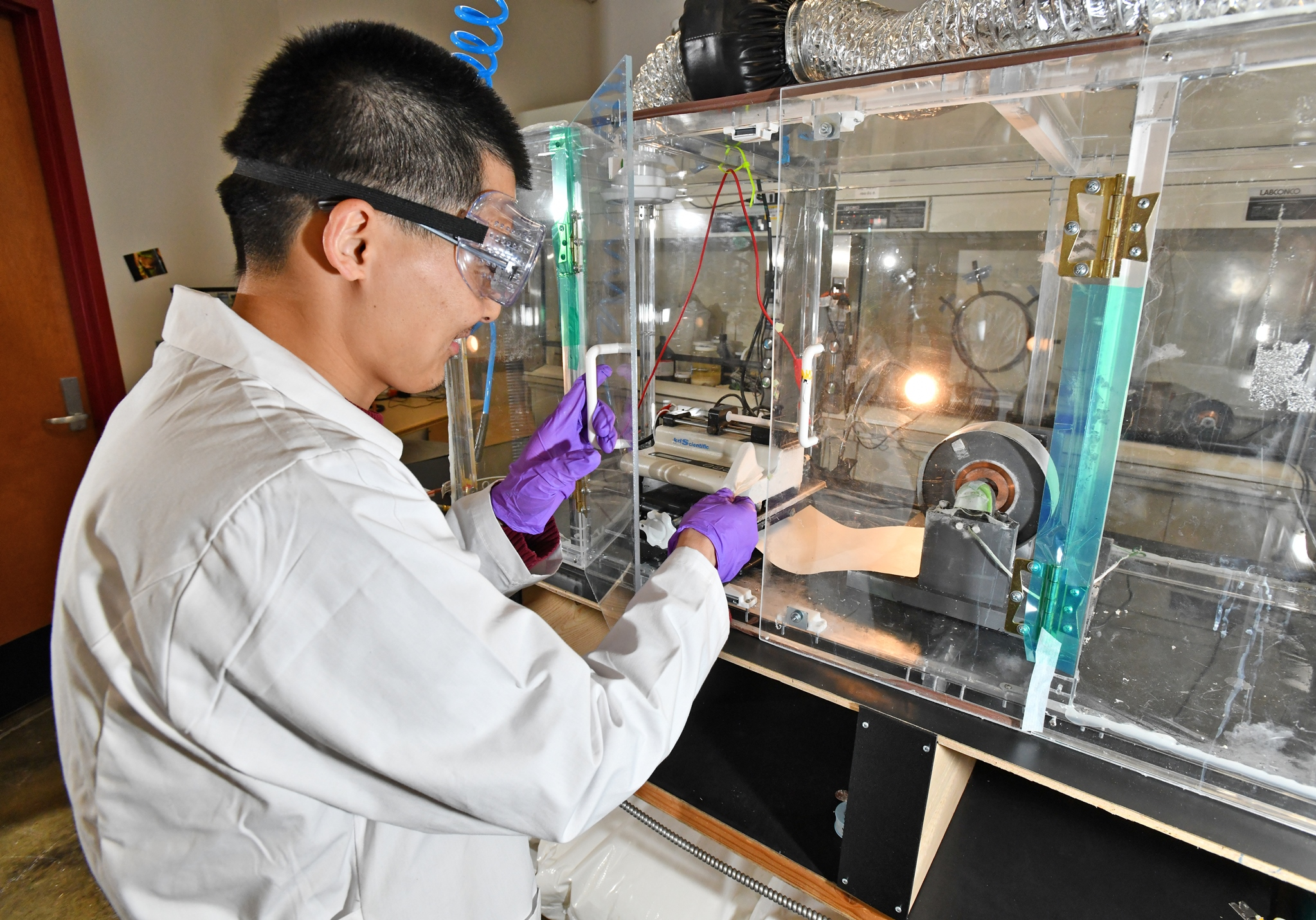 Dr. Fei Wang, AAI lead chemist, demonstrates lab-scale electrospinning at the Bounce Innovation Hub. A high voltage is applied at the tip of a syringe containing a polymer liquid. As the voltage is increased, the liquid deforms toward the nearest grounded surface and ultimately ejects as a thread with rapidly increasing surface area to offset the electrical charge. Formulations are carefully tuned to balance between the effects of charge build-up, which extend the jet and drive the reduction in diameter, with surface tension, which pulls back and may result in bead or droplet formation. The small collector on the right is used for rapid prototyping of new polymer blends and basic research, particularly the relationship between fiber structure and performance.