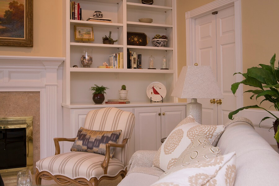 Use accent pillows in a mix of patterns and display meaningful objects on bookshelves to create an inviting room.