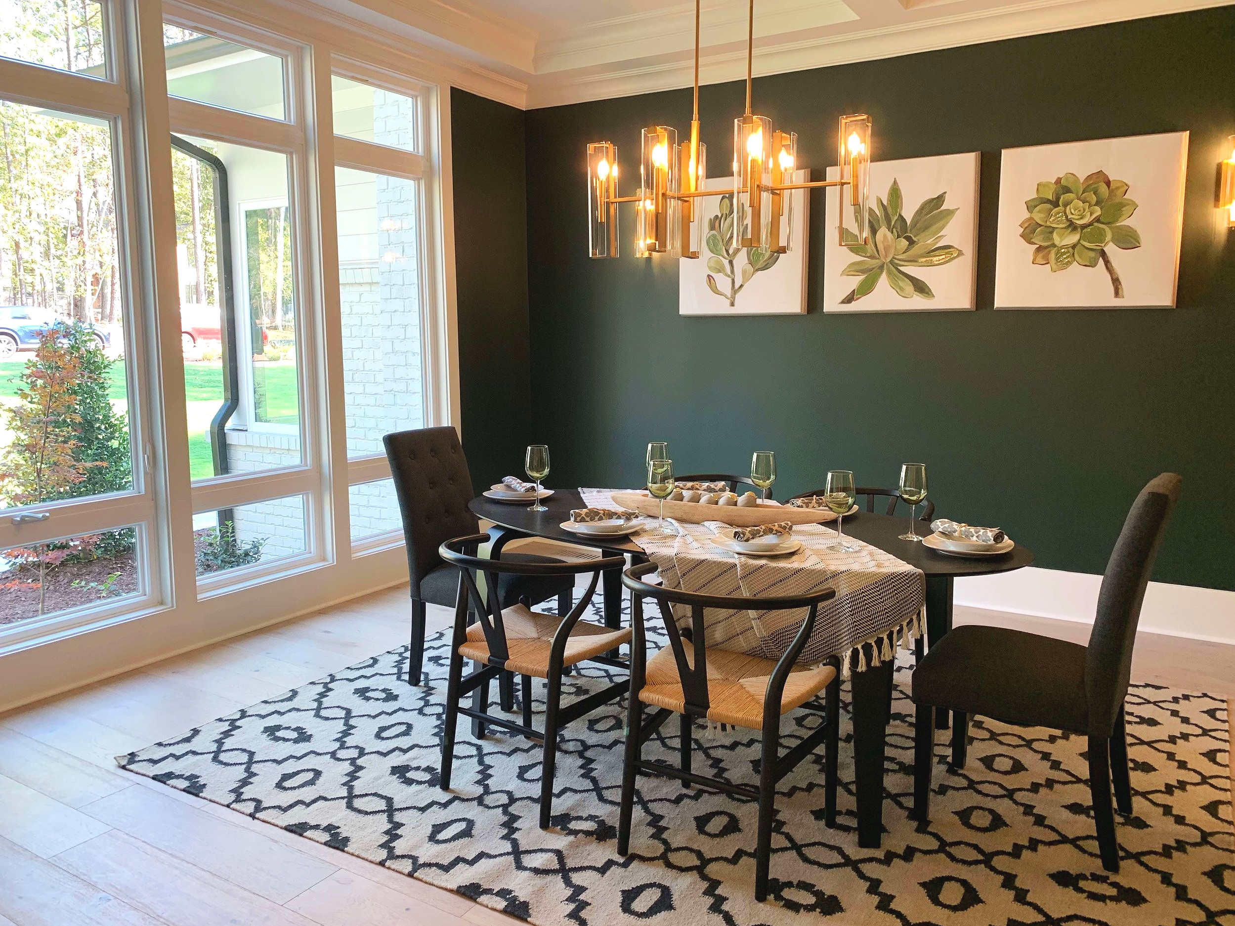 Dining room with rug, oval table, modern chairs, large windows and dark painted accent wall.